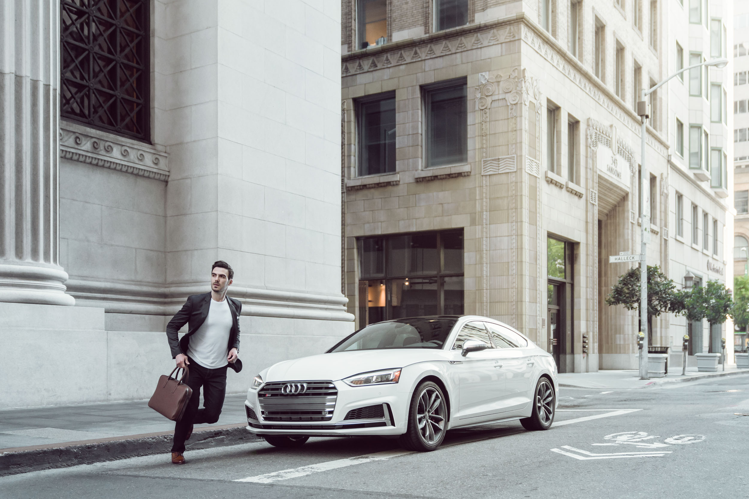 A male in business attire runs across street near his white Audi S5 Sportsback