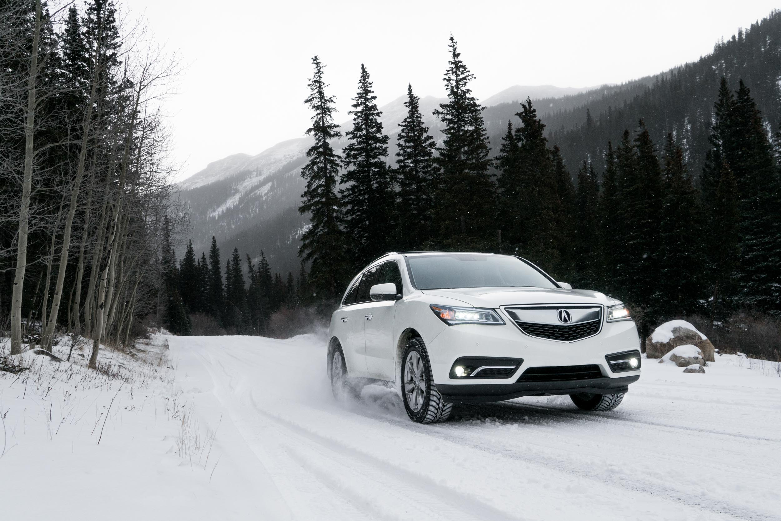 White Acura MDX drives up a snowy mountain road in Colorado