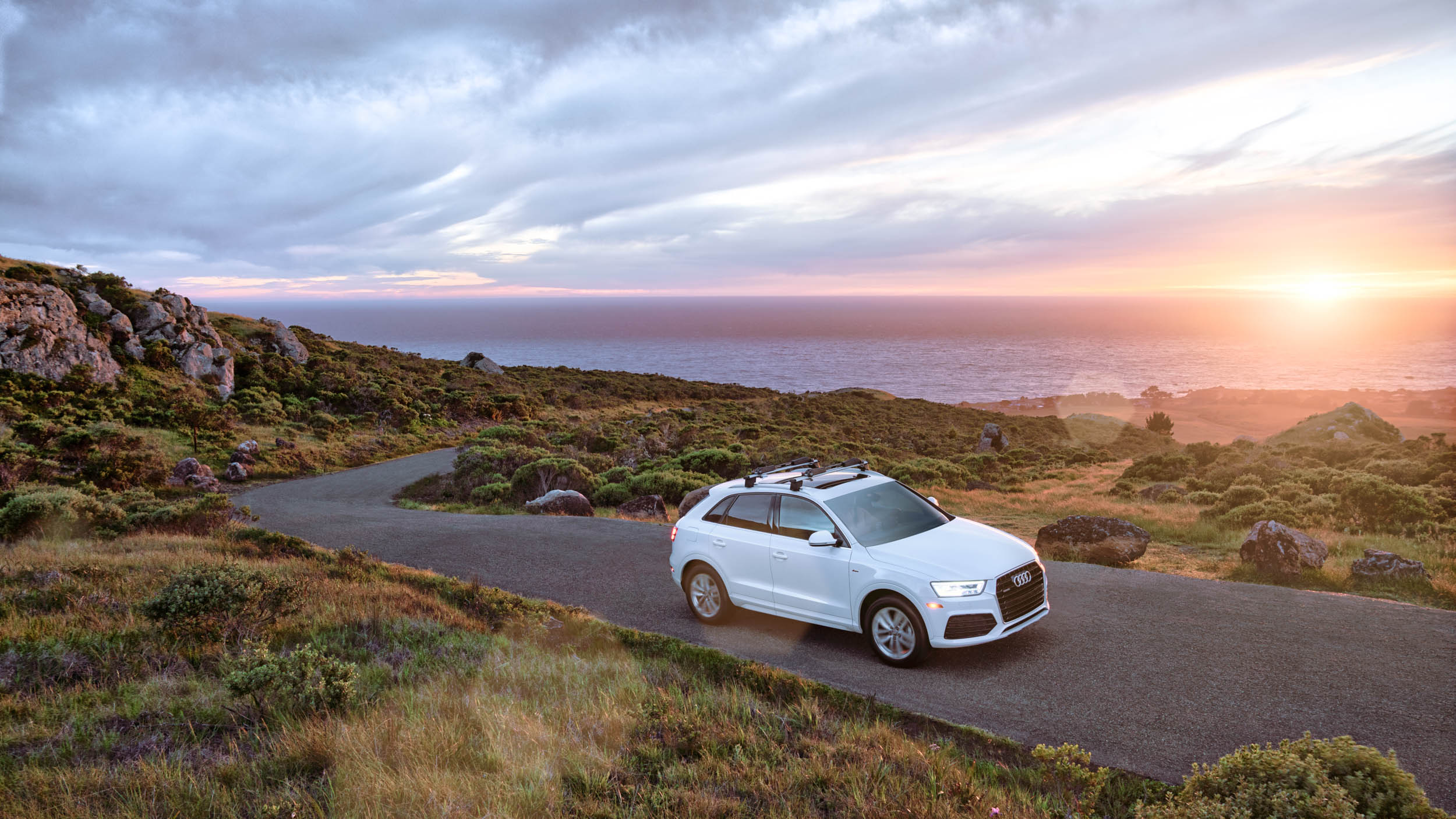 White Audi Q3 drives up curvy coastal road with sun setting over the Pacific Ocean
