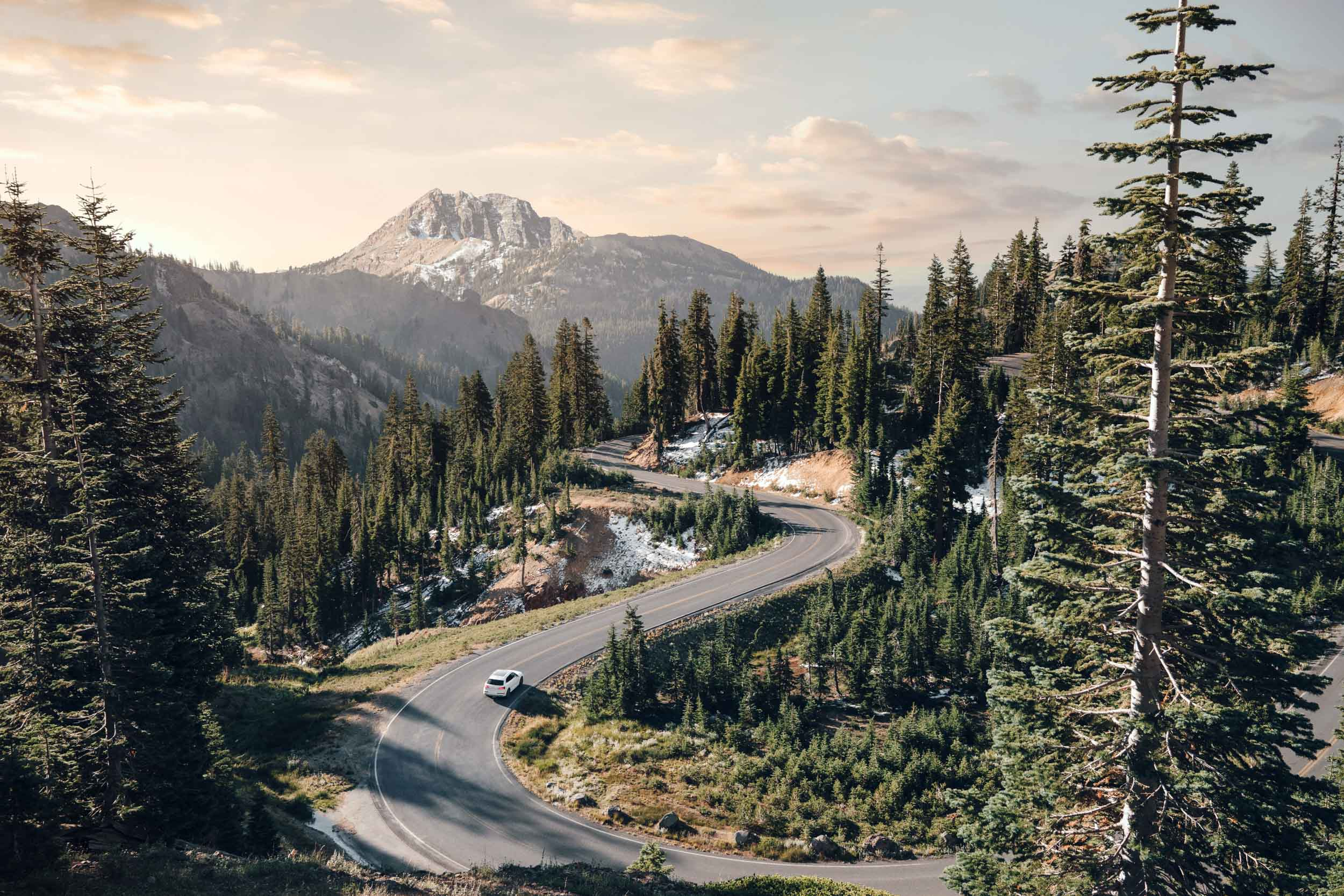 White Audi Q7 drives down a curvy road with Mount Lassen in the background