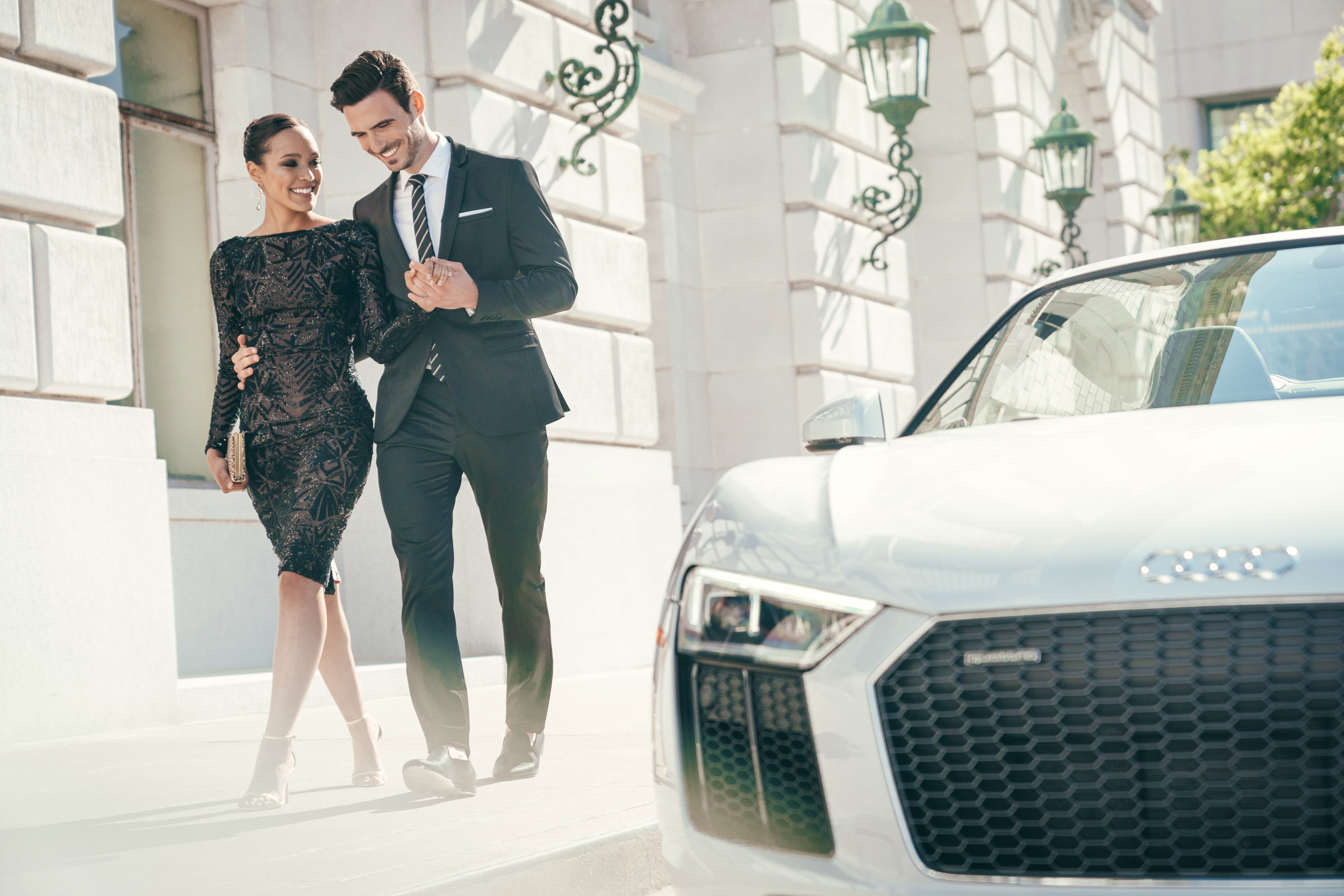 Couple in suit and dress walk together near their white Audi R8 Spyder in front of the San Francisco Opera