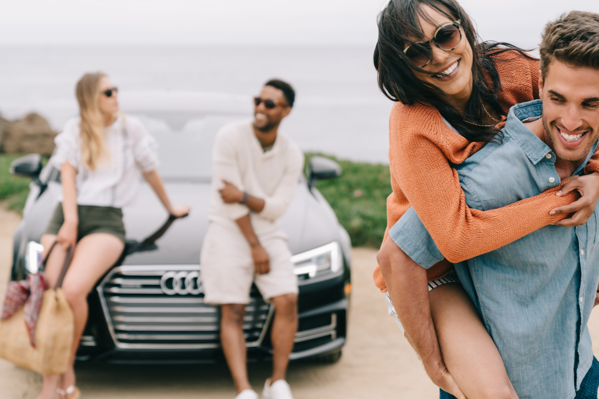 Four friends goofing around by their black Audi A3 at the beach