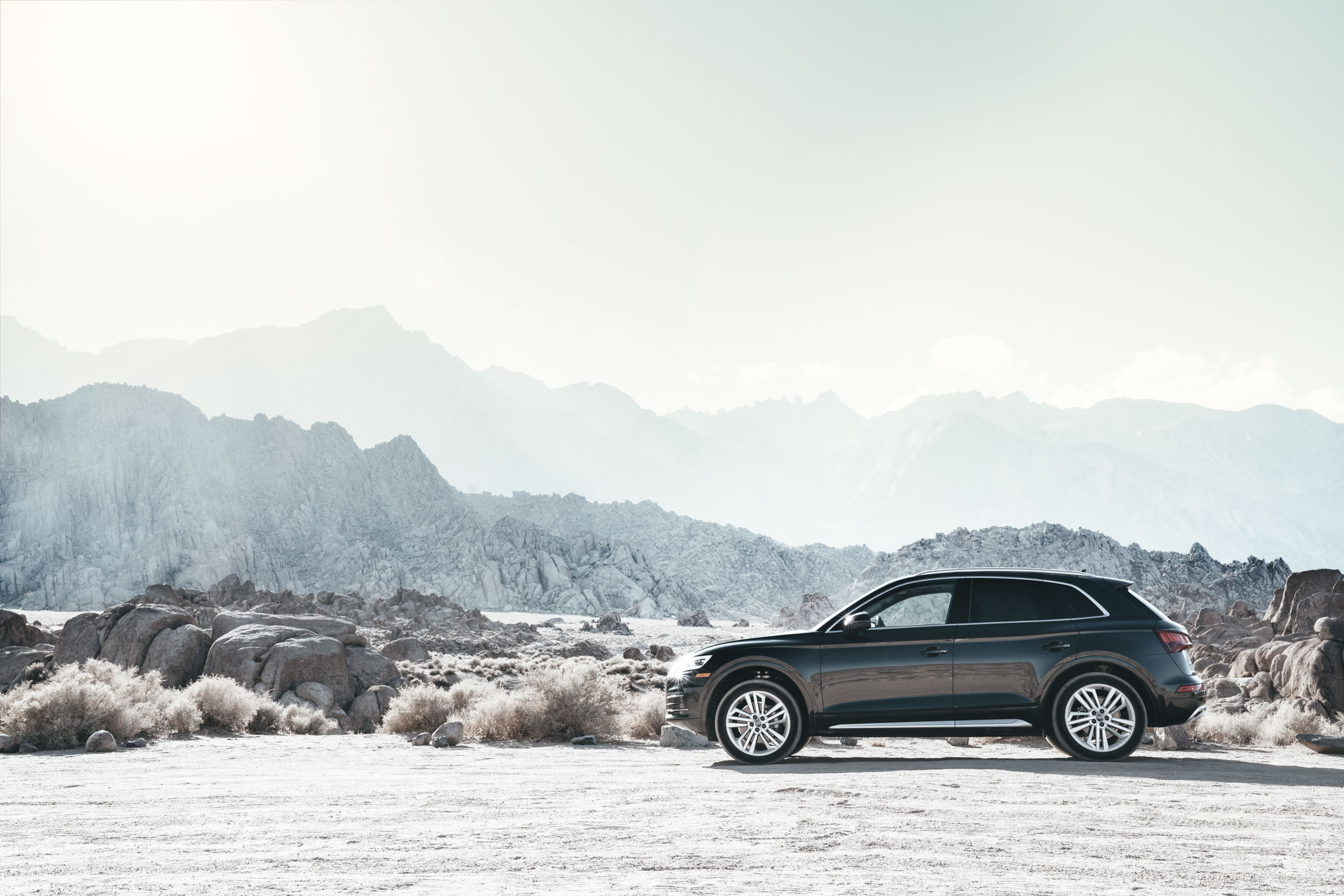 Black Audi Q5 sits in a bleak desert environment with mountains in background
