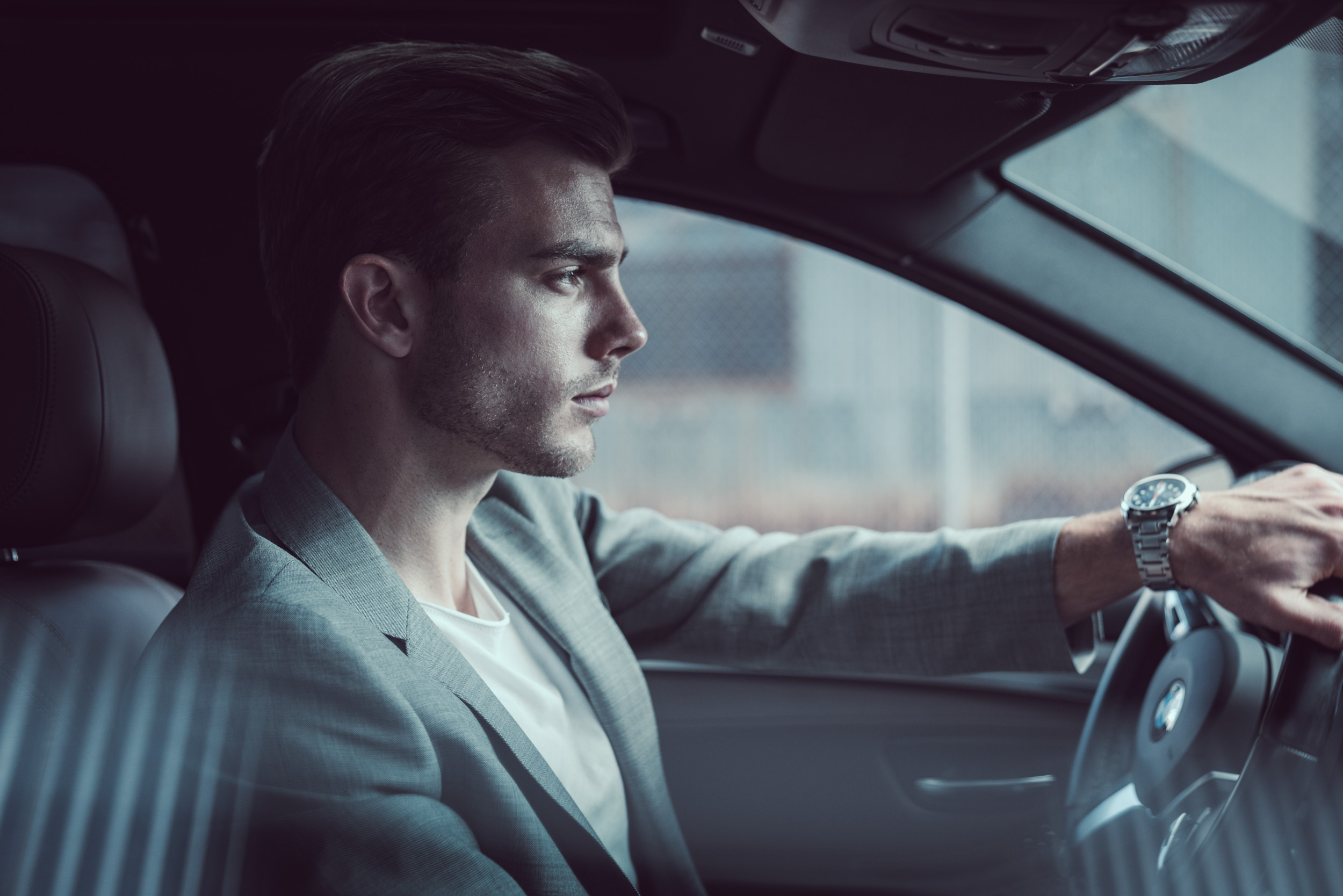 Fashionable male model in grey suit inside BMW