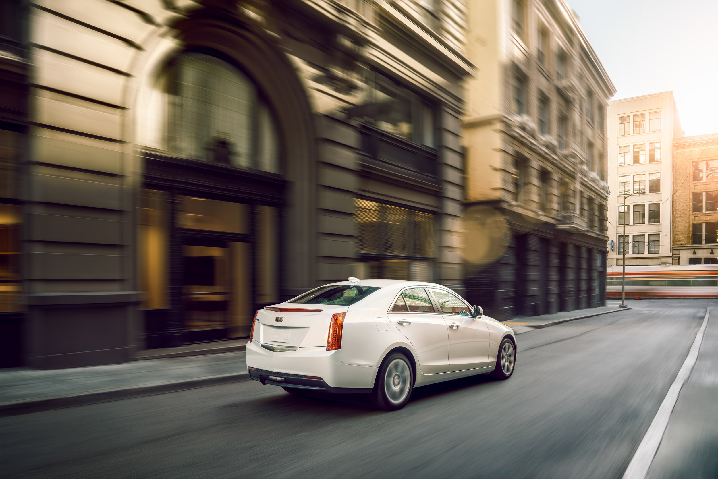 White Cadillac ATS driving down elegant road in San Francisco