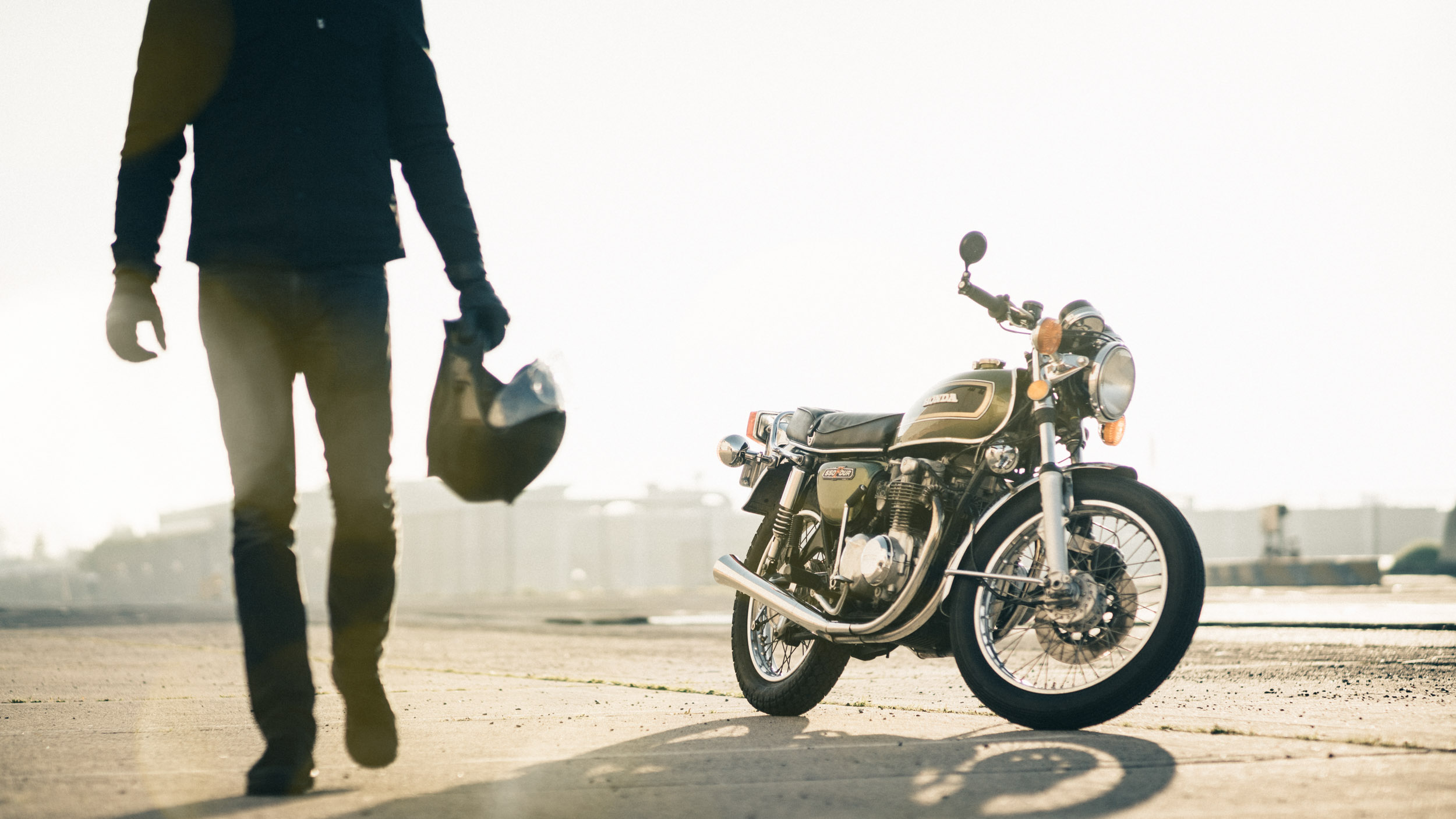 Male in black clothing walks away from vintage Honda CB550 motorcycle on a tarmac