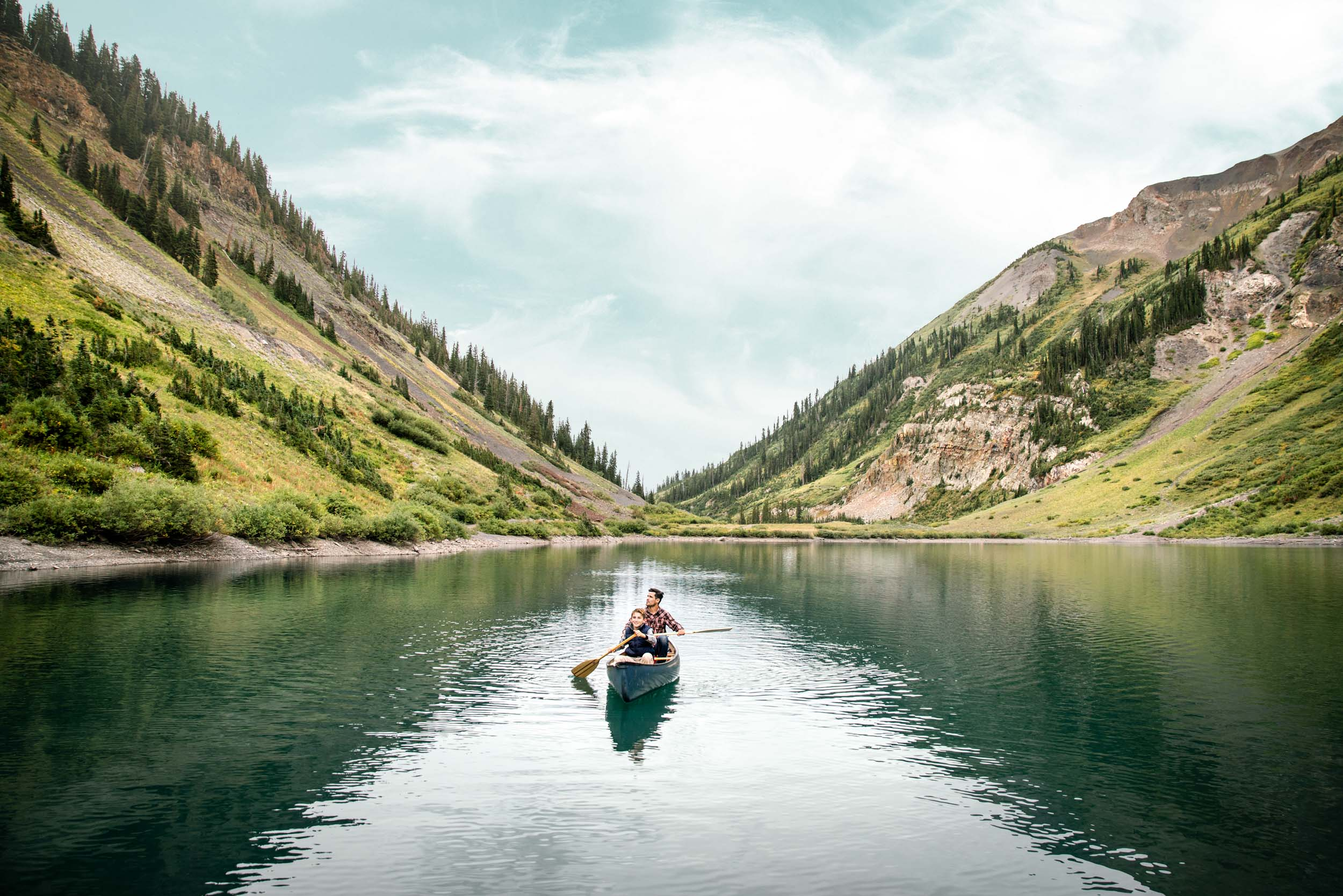 Father and son canoeing together in a mountain lake in the Colorado rockies.