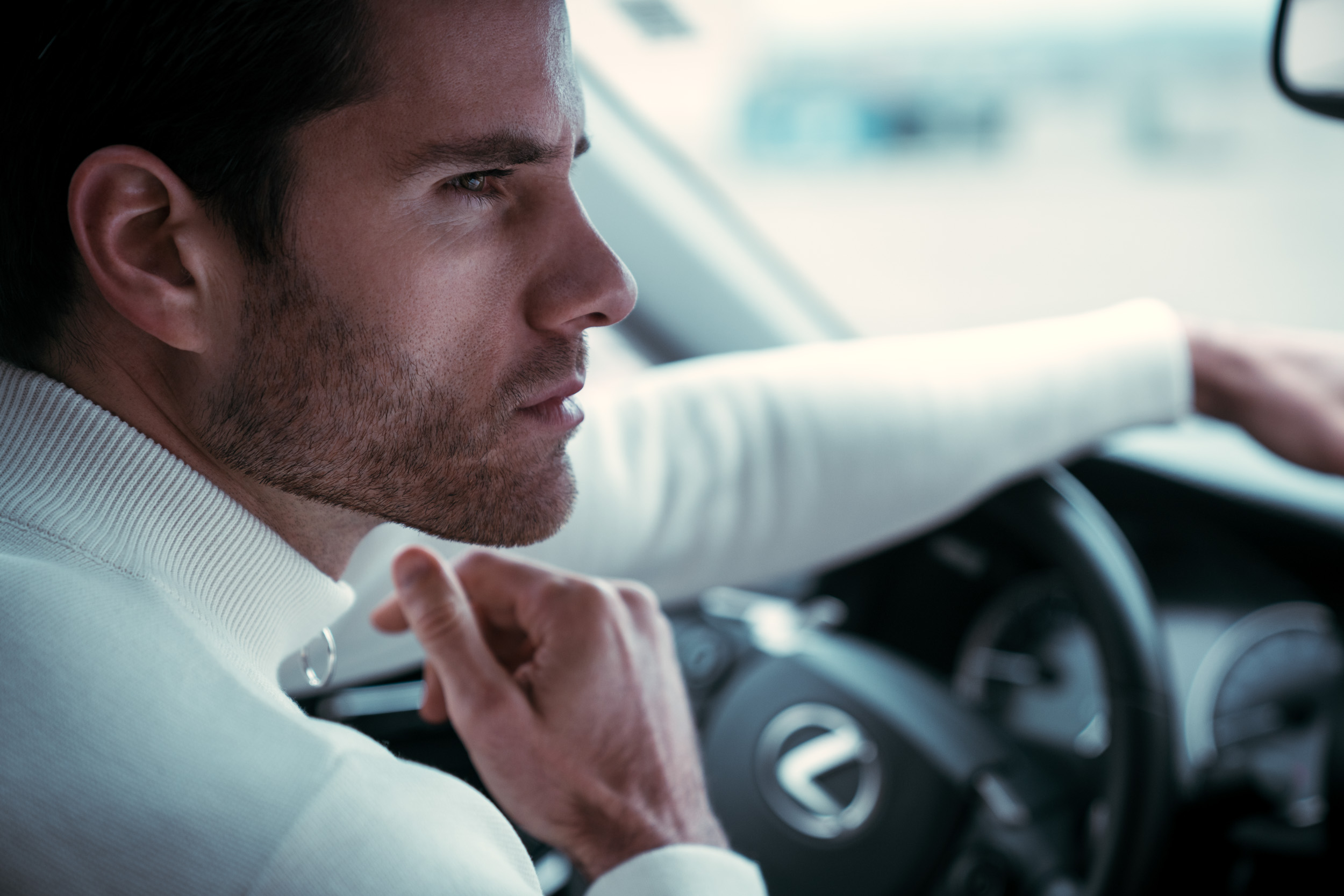 Man in white turtleneck sweater sits inside his Lexus