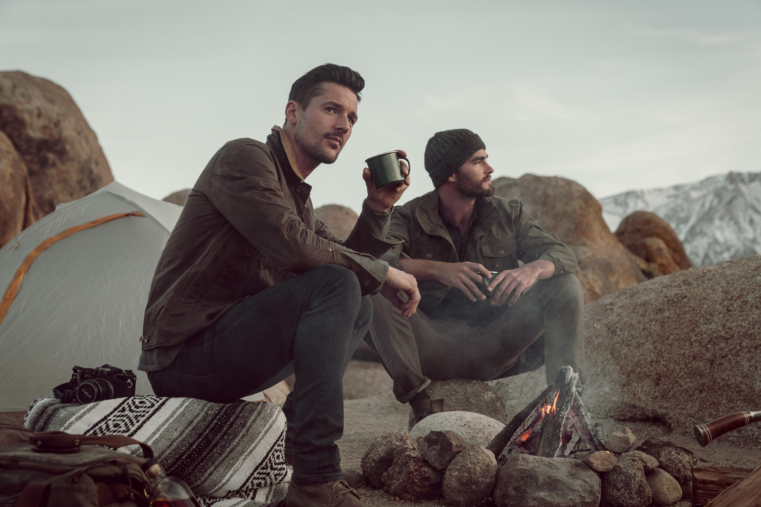 Two rugged outdoorsmen enjoying a drink by the fire at twilight.