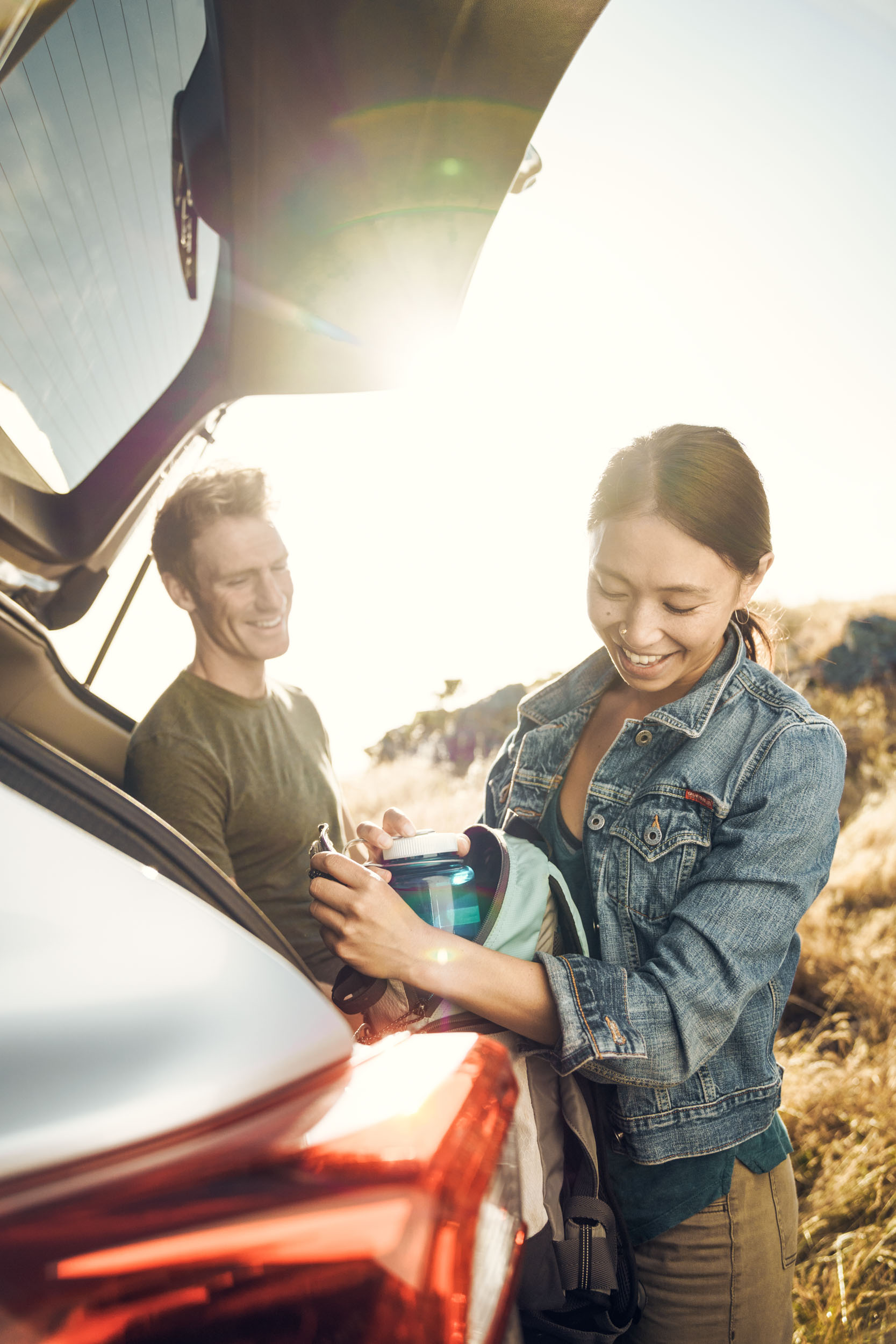 A female laughs were her male friend as they prepare their hiking gear at the tailgate of their Subaru Crosstrek