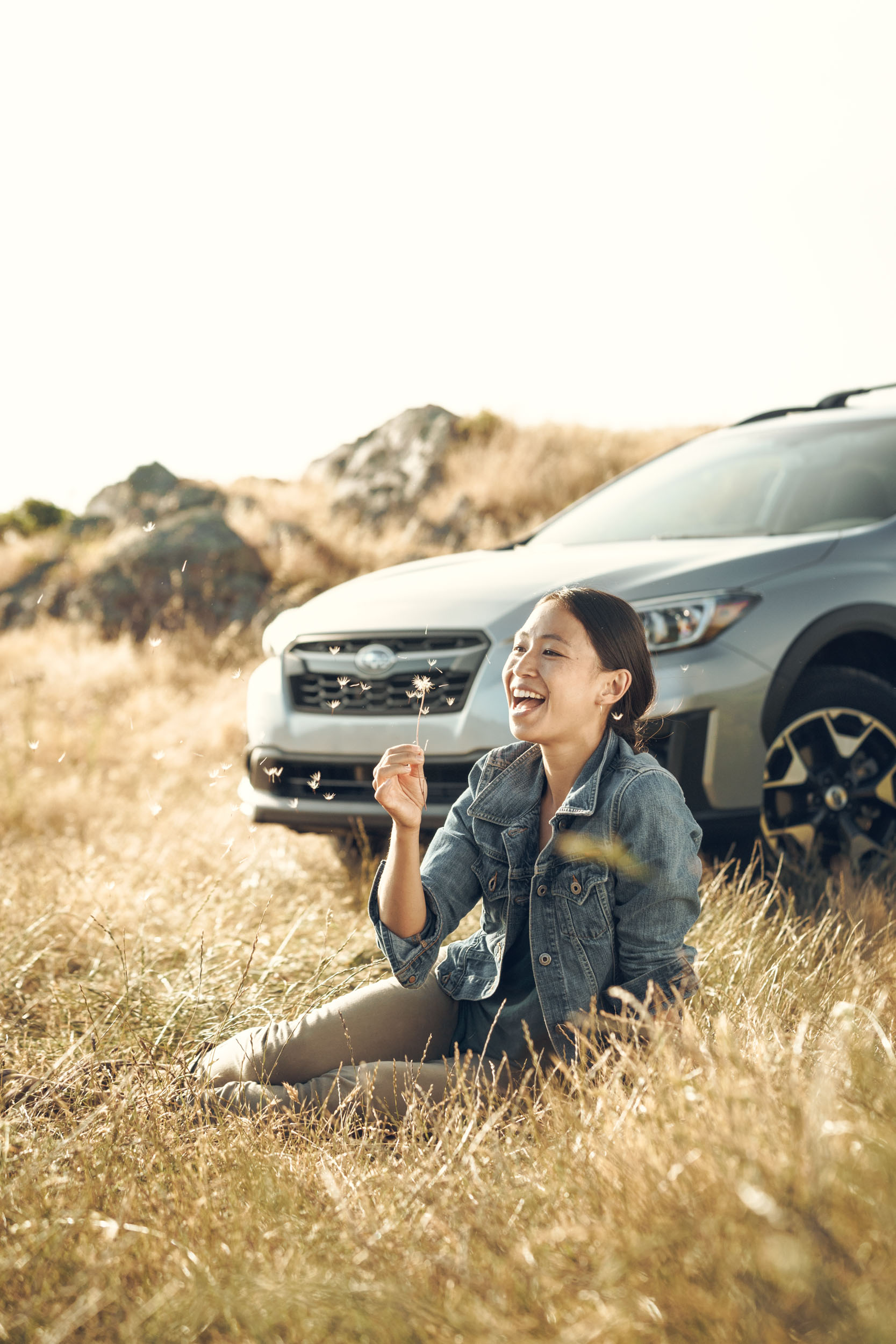 A female sits in tall golden grass and blows on a dandelion in front of her silver Subaru Crosstrek