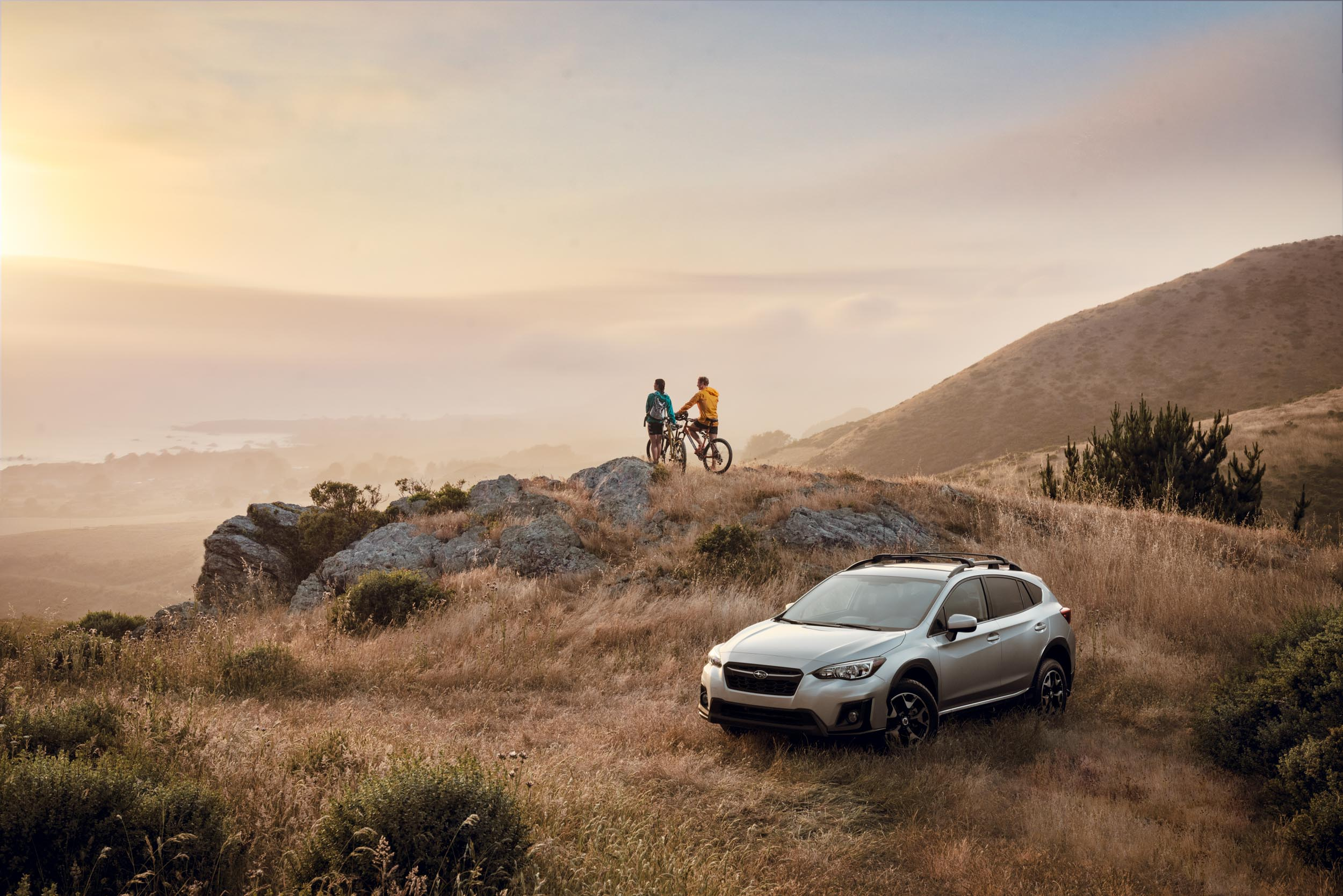 Two mountain bikers watch the sunset near their Subaru Crosstrek