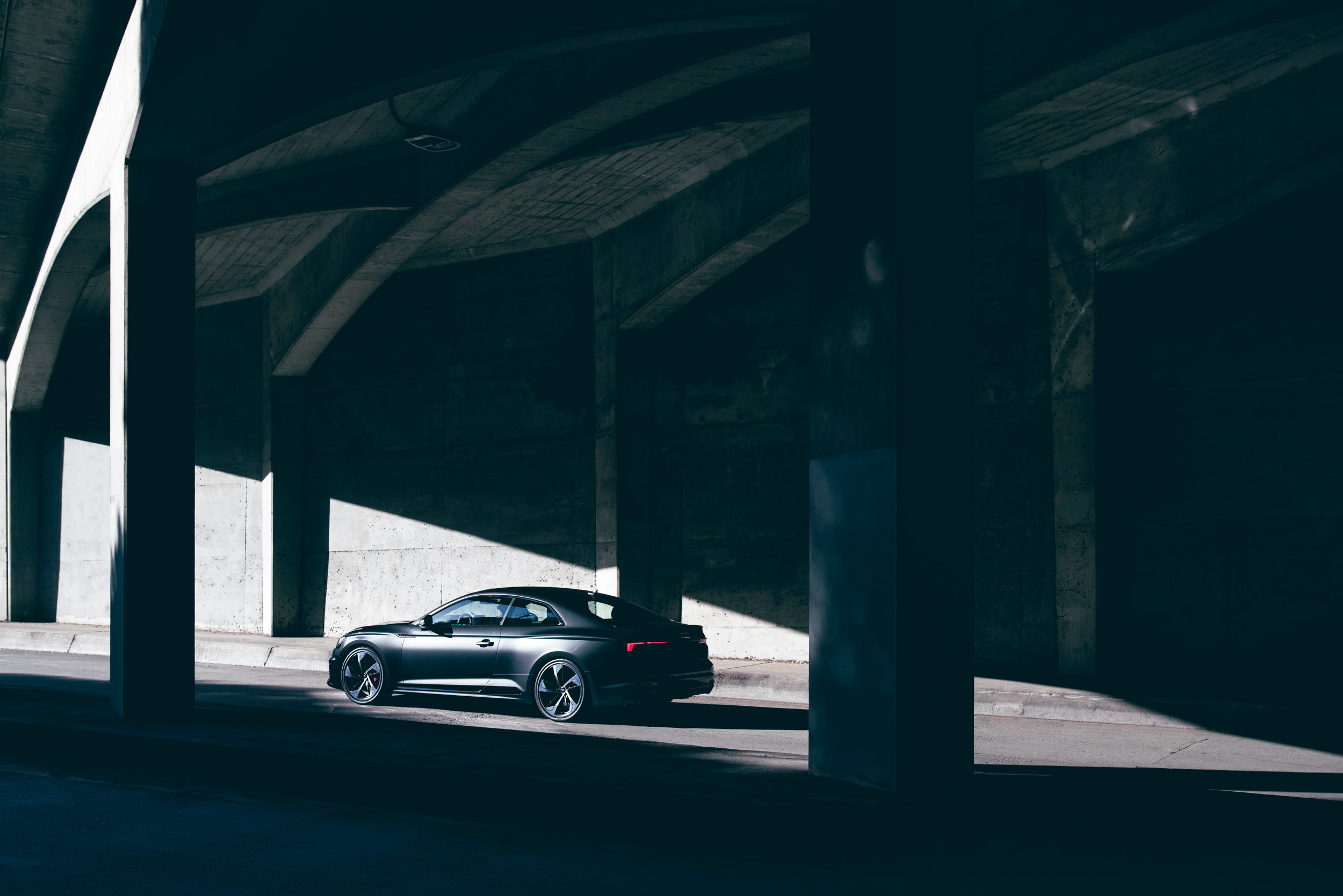 A grey Audi R S5 drives emerges from the shadow of a concrete bridge
