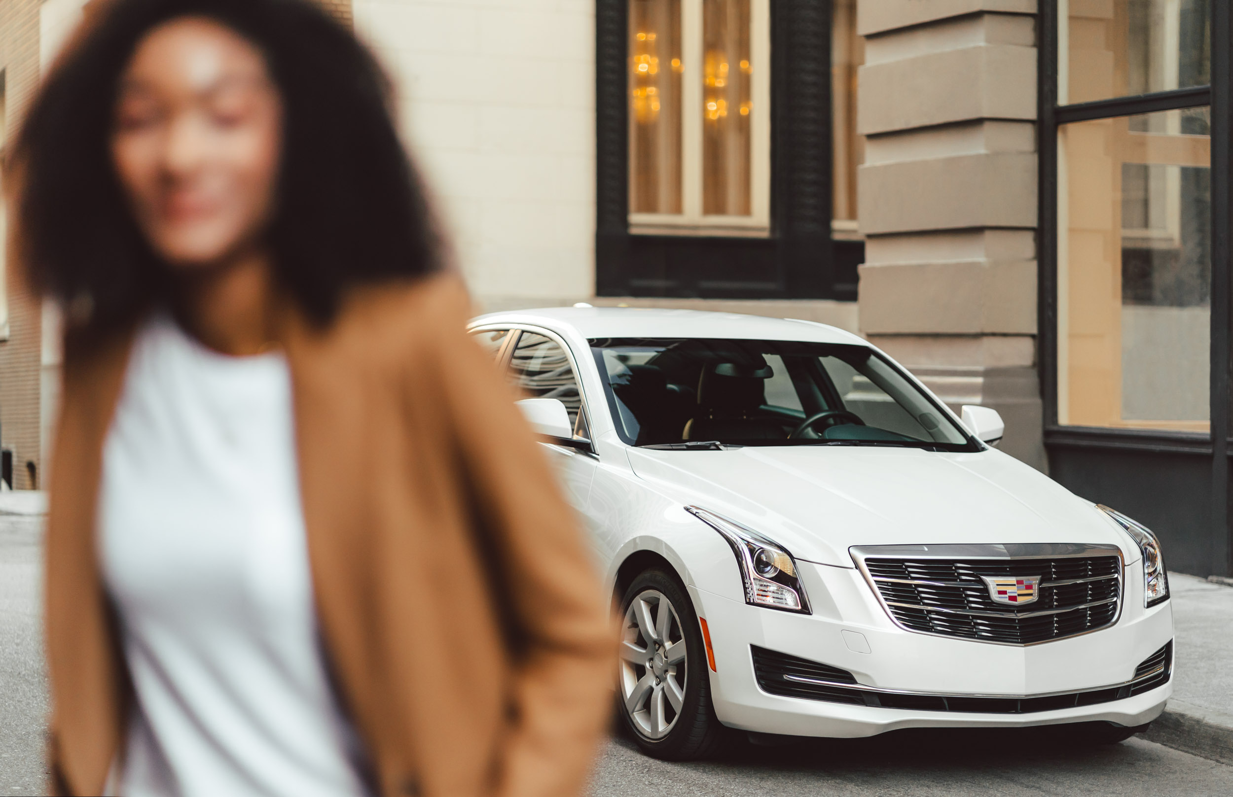 White Cadillac ATS parked in an alley with a female model in the foreground