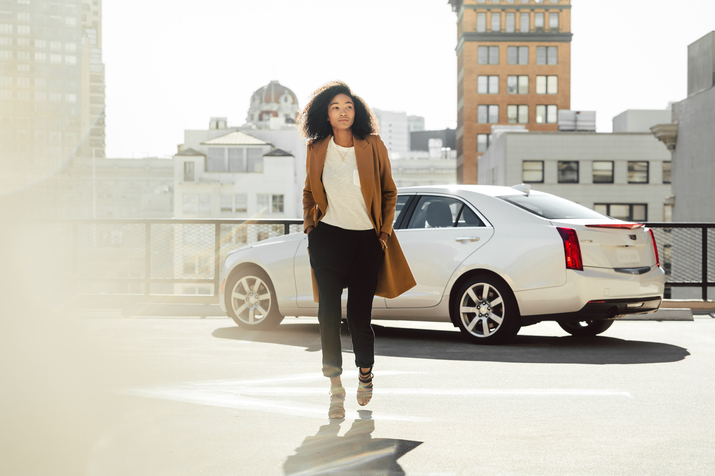A female models walks confidently across a parking lot rooftop with her white Cadillac in the background