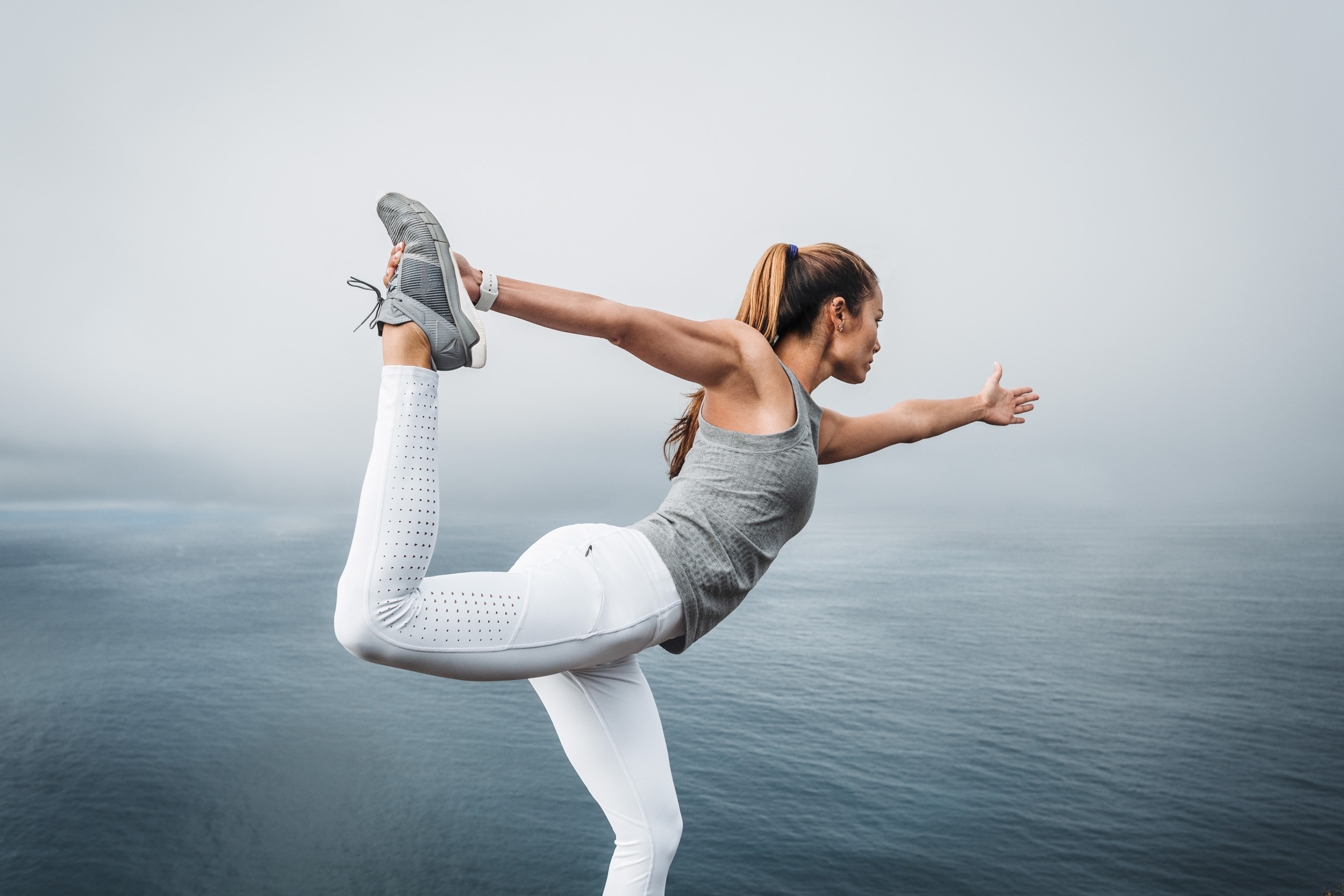 Female athlete wearing white Athleta tights and grey shirt practices yoga on a cliff near a foggy ocean