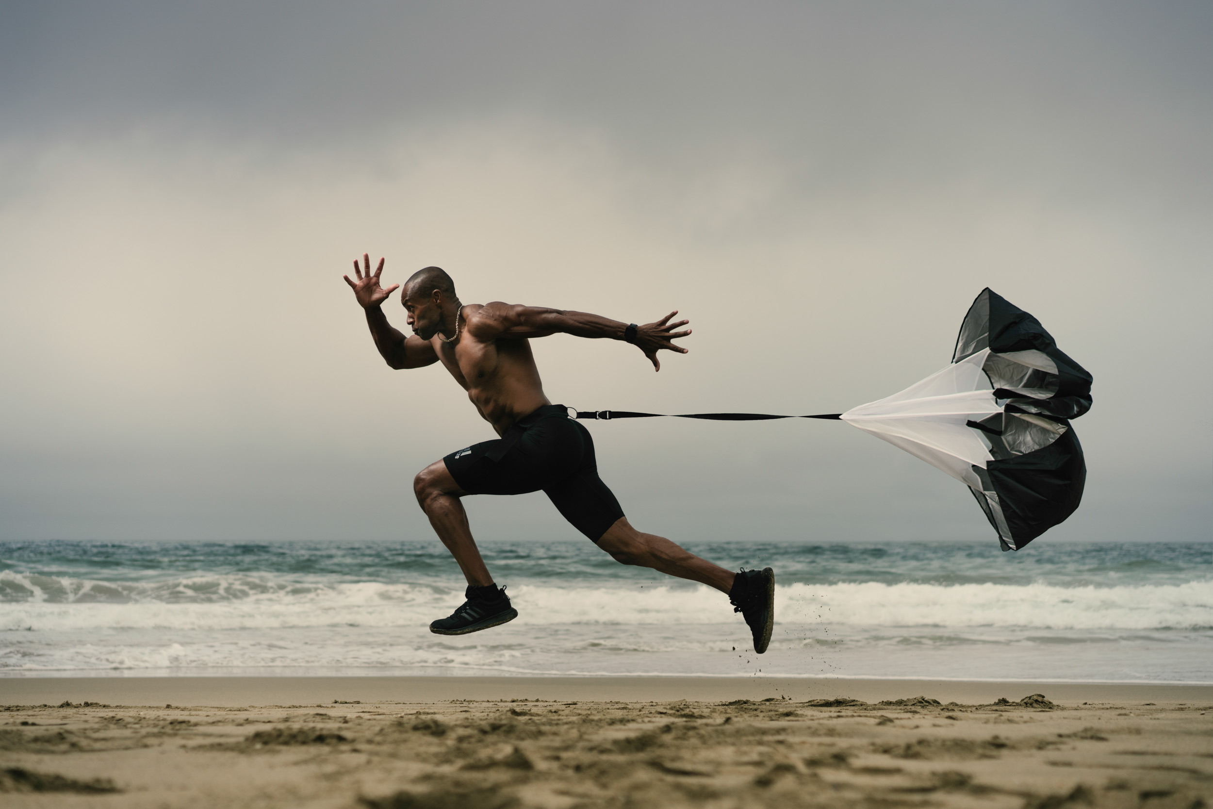 Male athlete with no shirt sprints with parachute during a morning exercise on a foggy beach