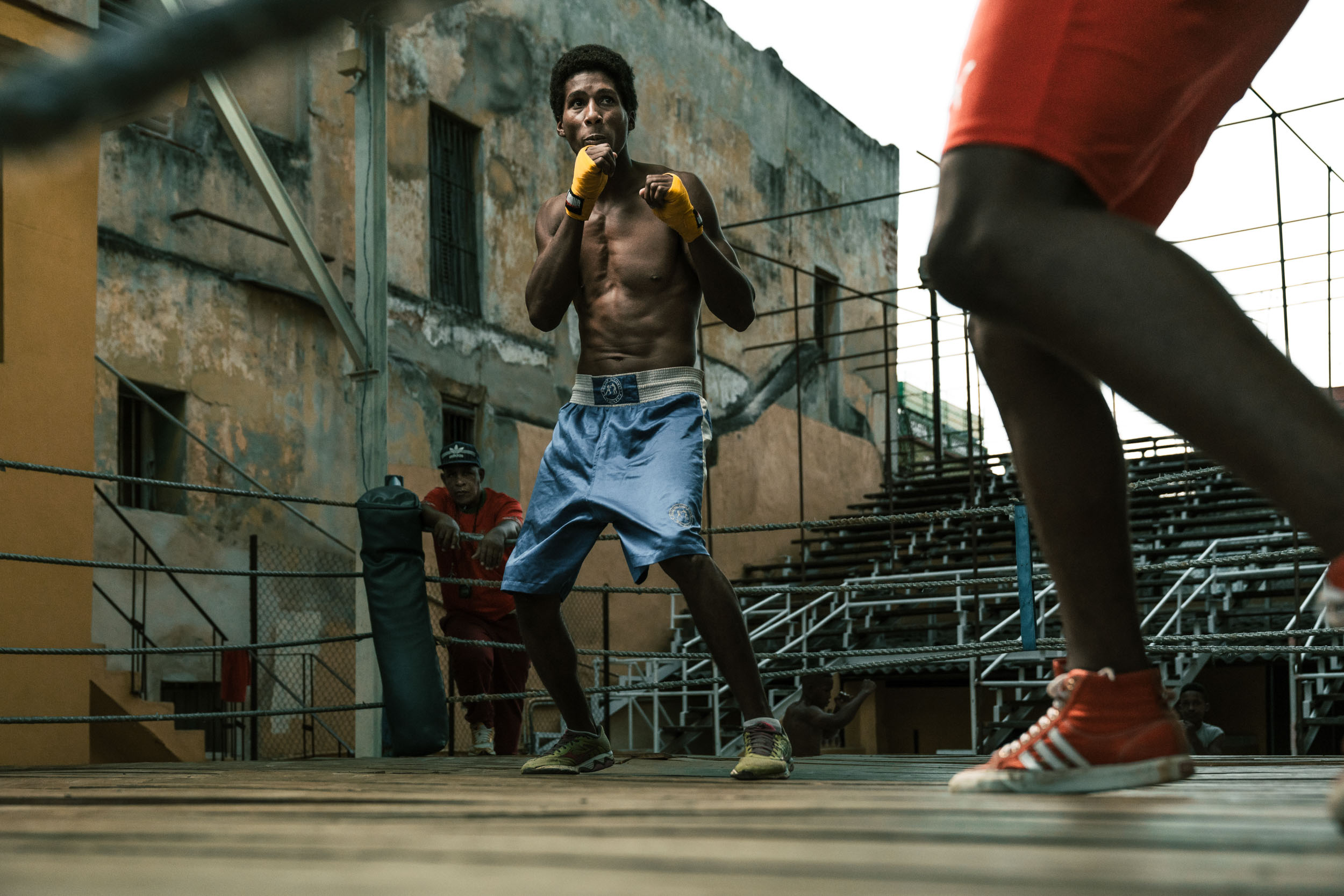 Male boxer in blue shorts spares with opponent in red shorts in Rafael Trejo boxing gym in Havana Cuba