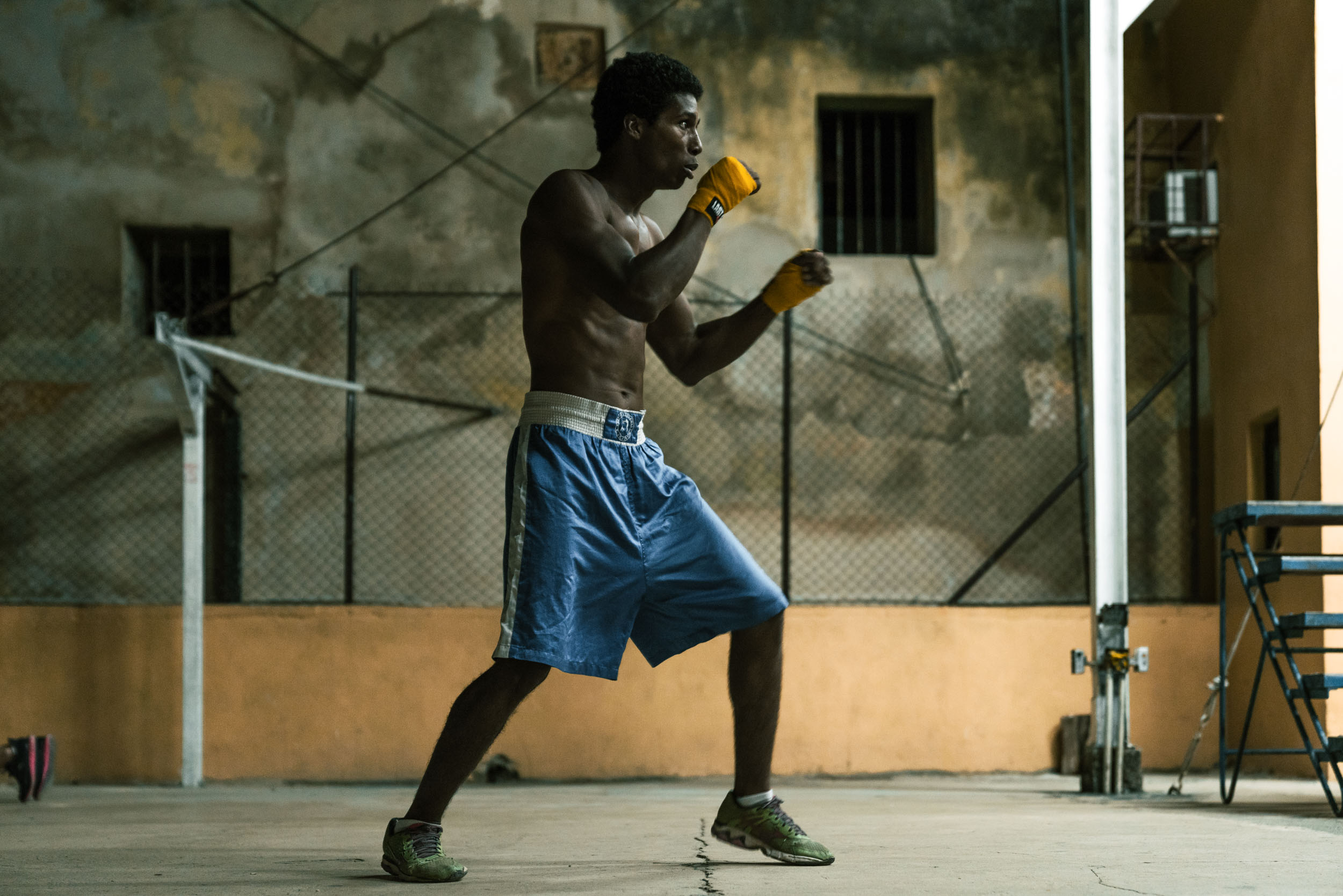 Male boxer in blue shorts shadow boxes in a dark boxing gym in Havana Cuba