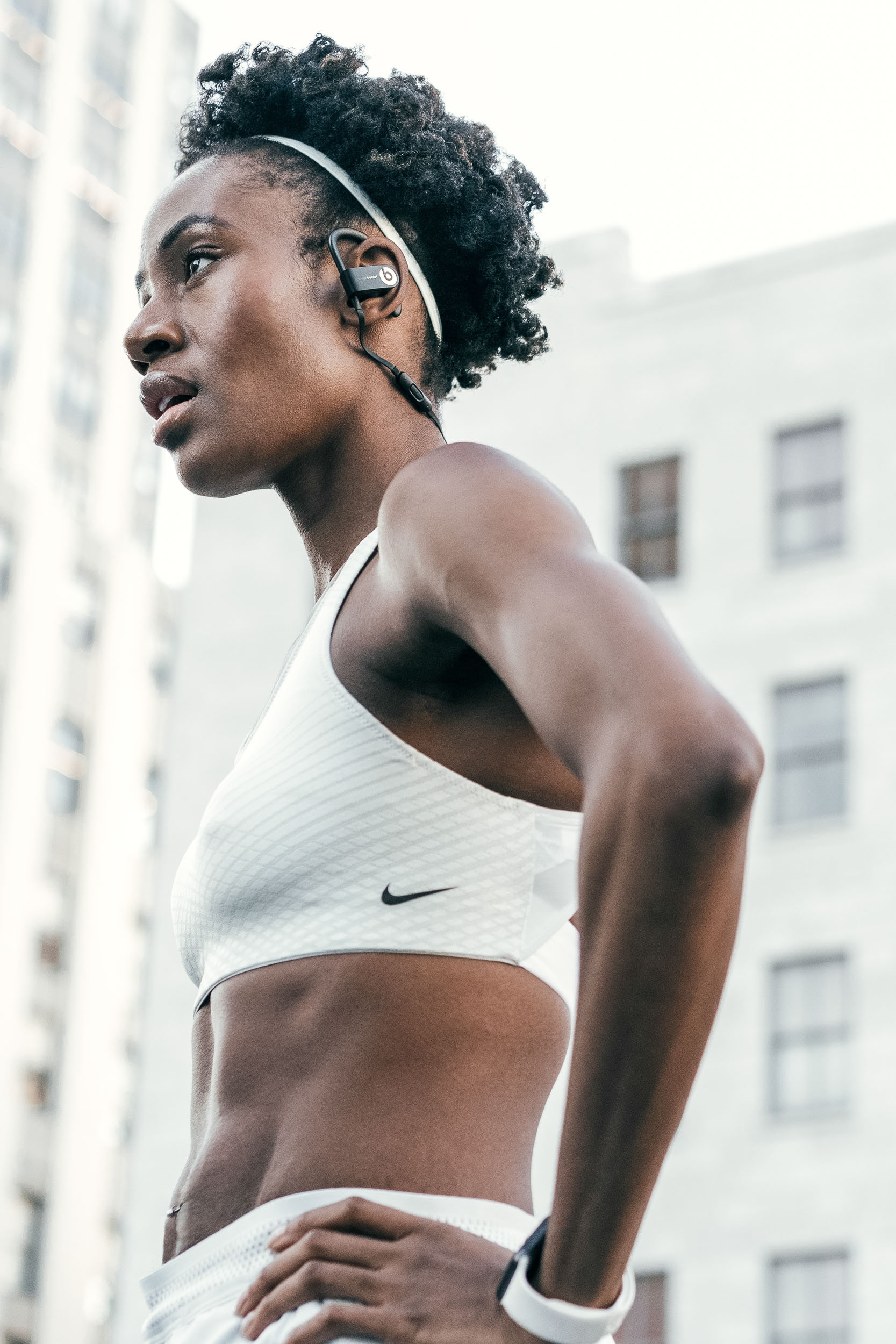 Female athlete in white Nike sports bra and shorts stands with hands on hips and looks into the distance