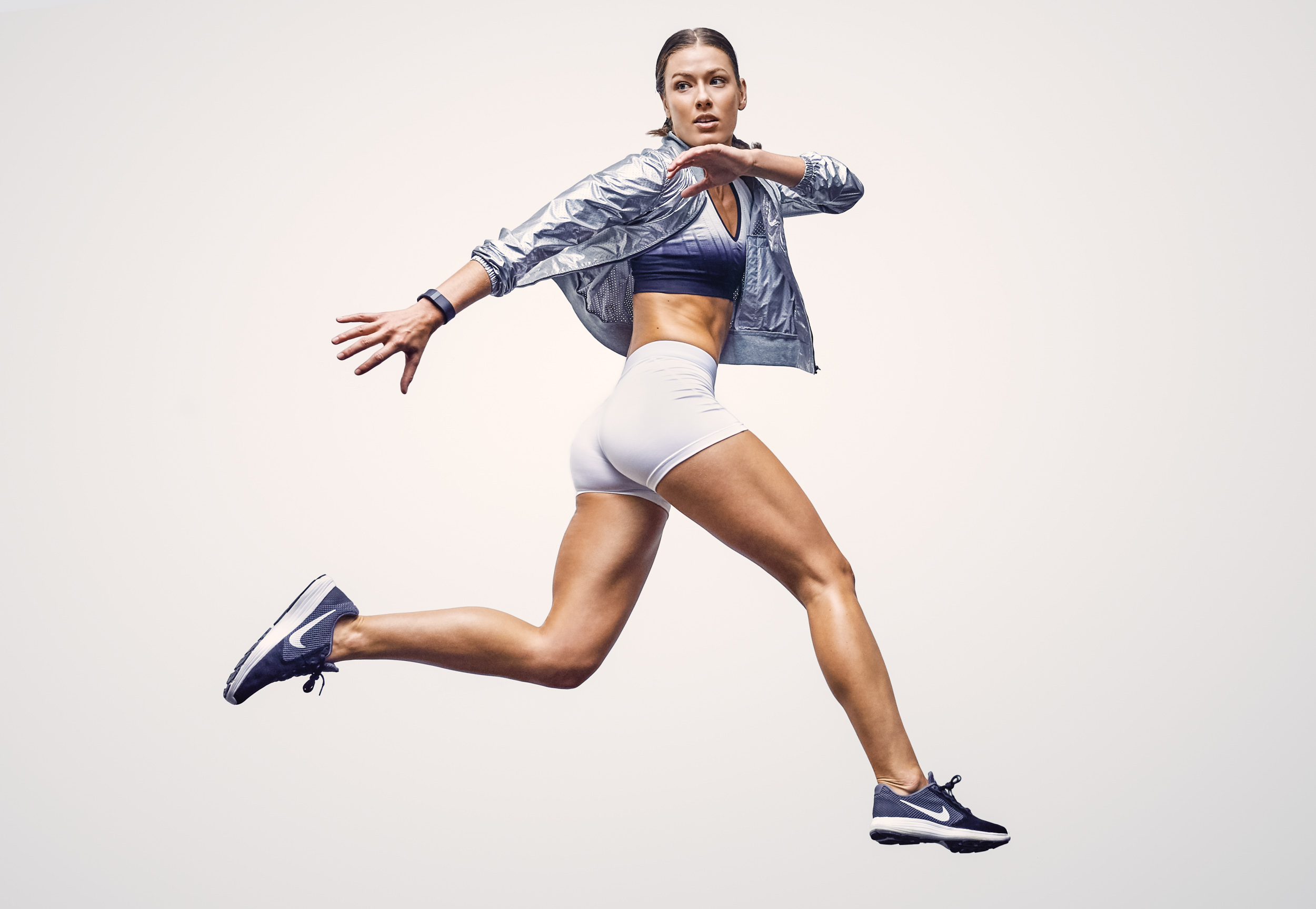 Female athlete in silver Nike track jacket and shorts jumps into the air in studio