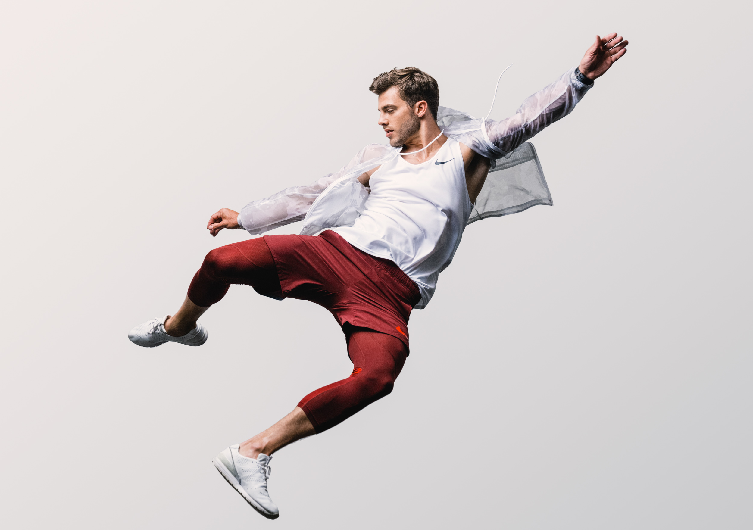 Male athlete in track jacket and red Nike pants jumps into the air in studio