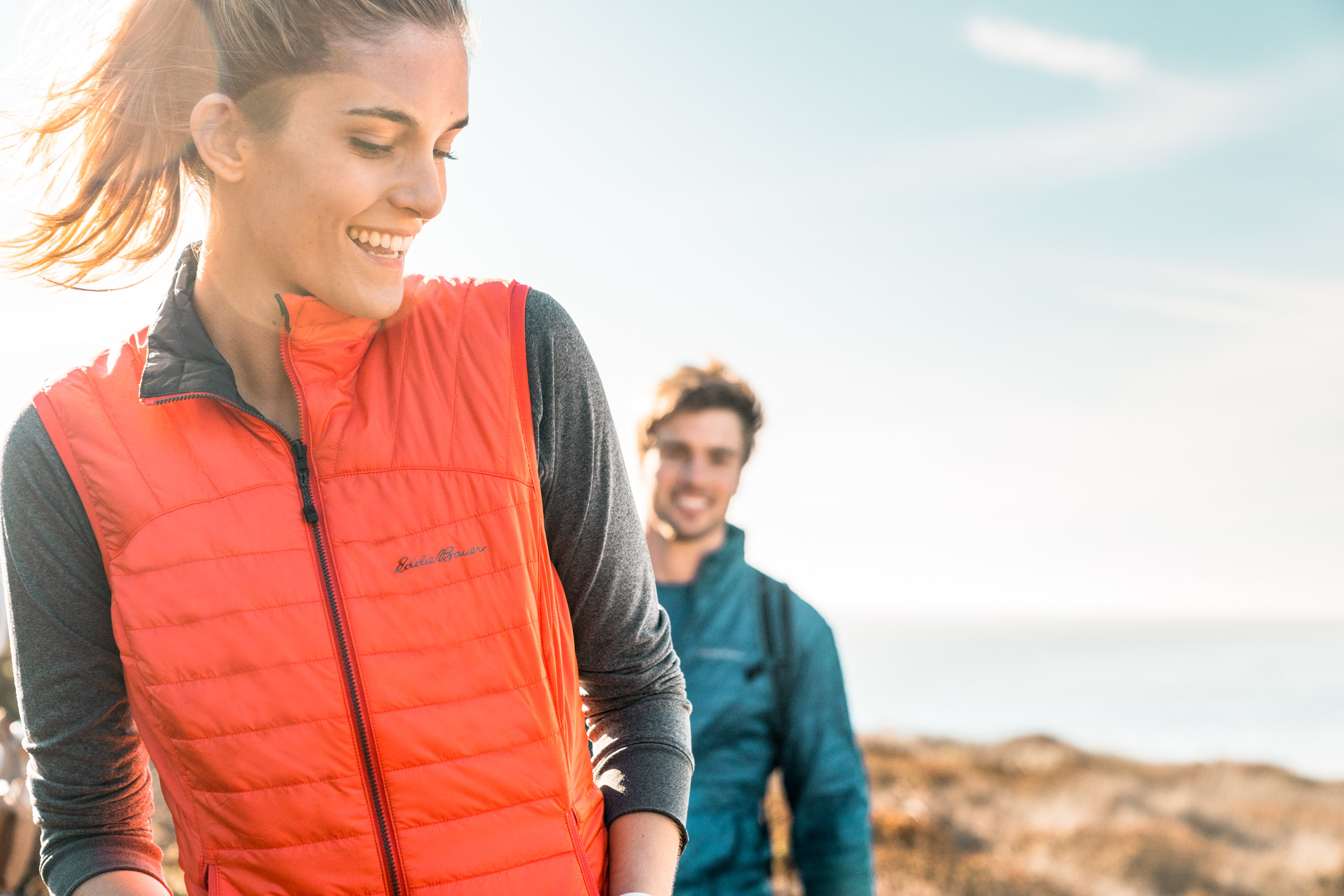Female athlete in red vest looks back at male athlete in blue jacket on the coast