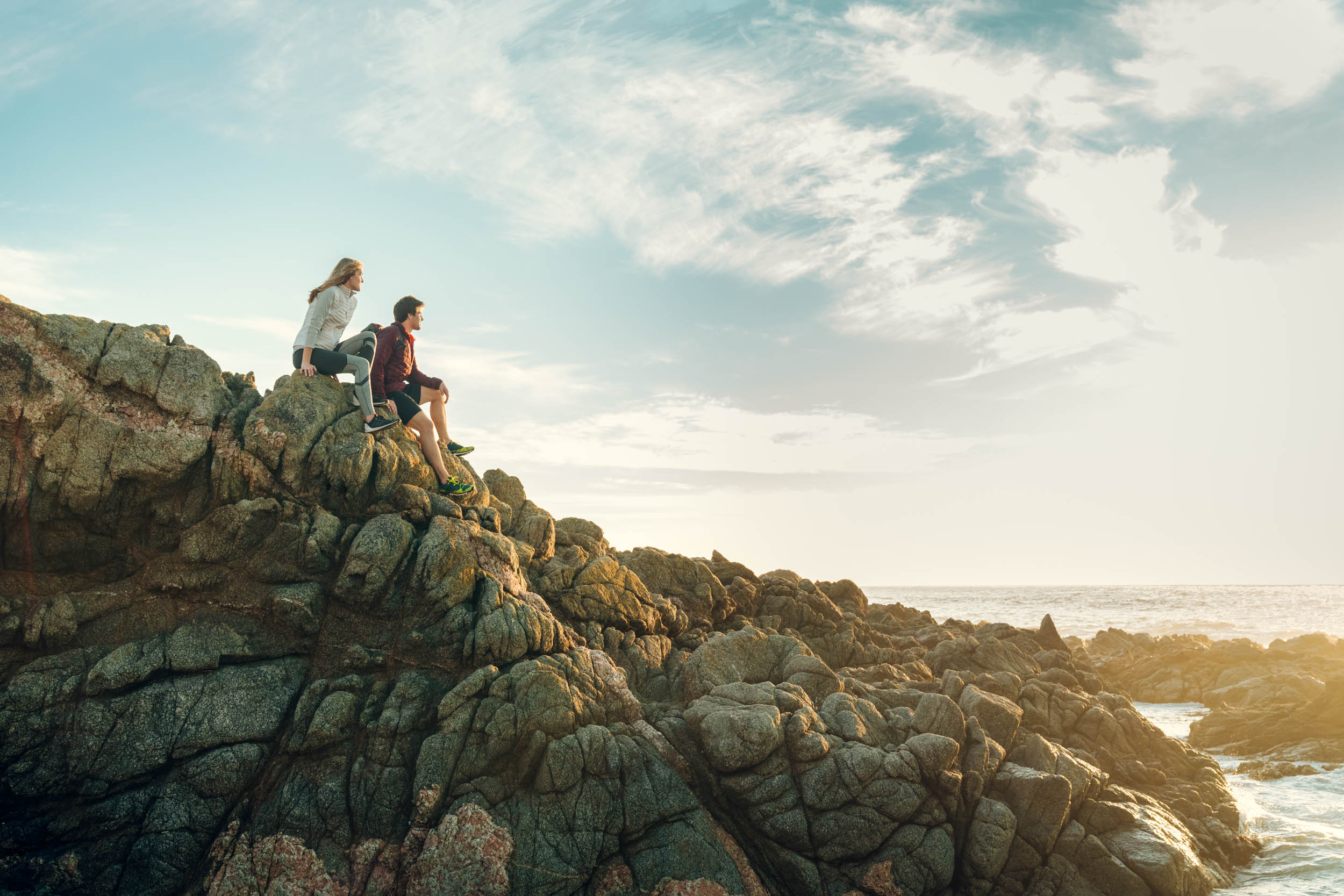 Female athlete sits next to male athlete on a rocky coast while watching the sunset