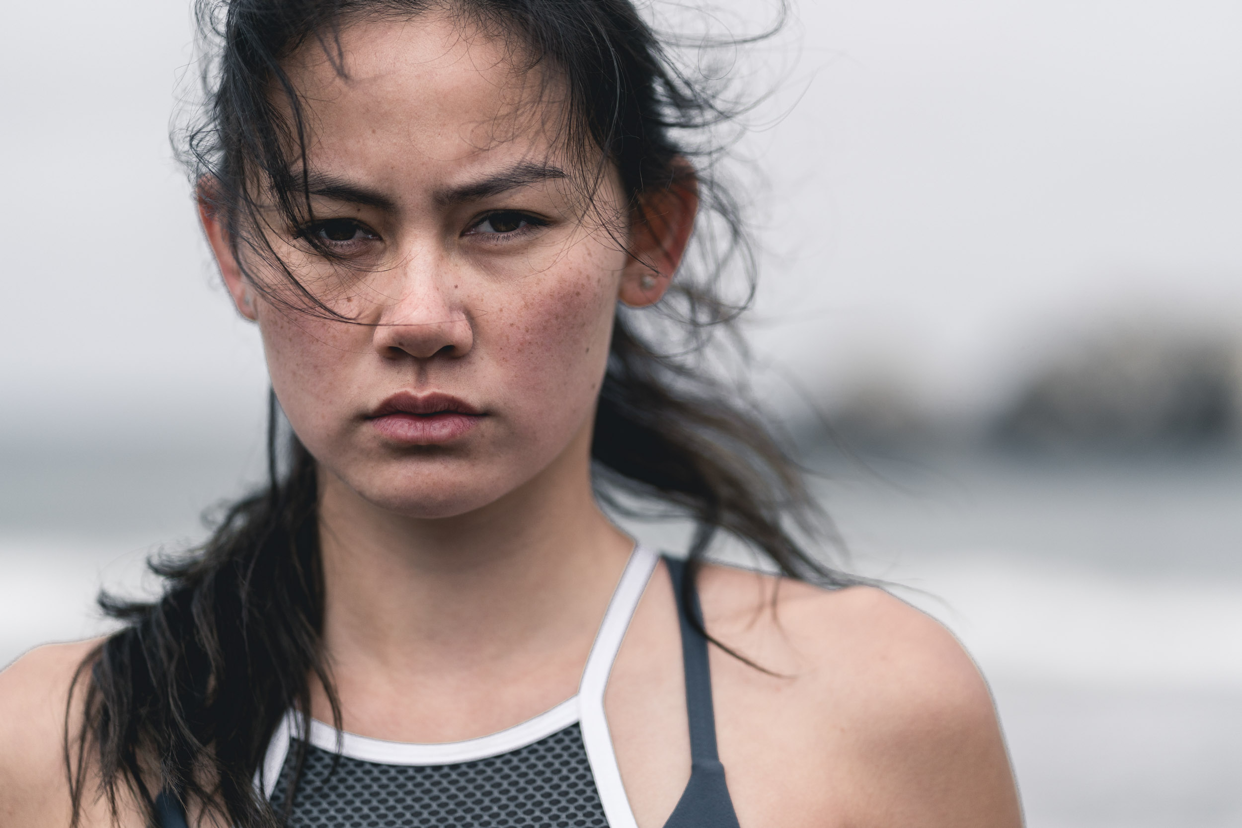 Intense portrait of female athlete at Sutro Baths on a foggy and windy morning