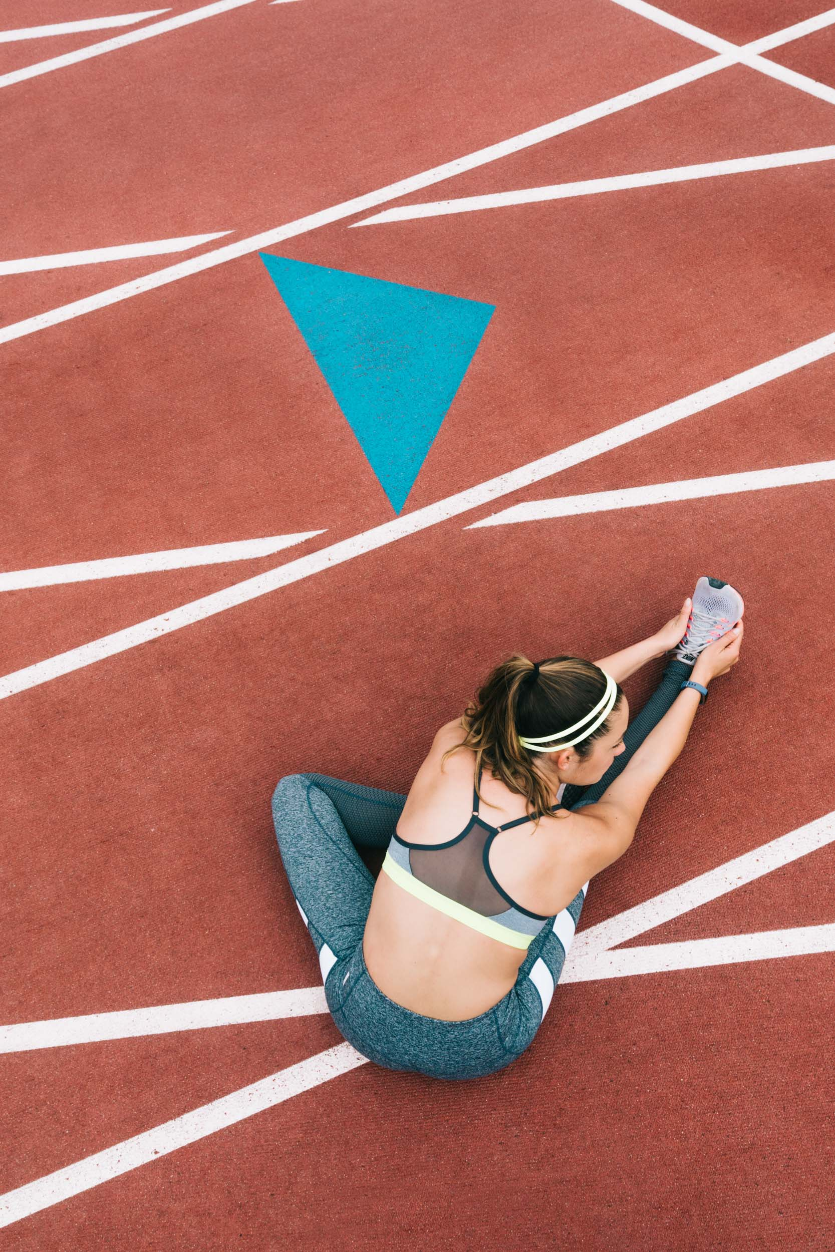 Overhead view of female athlete wearing sports bra and pants stretching on a red track