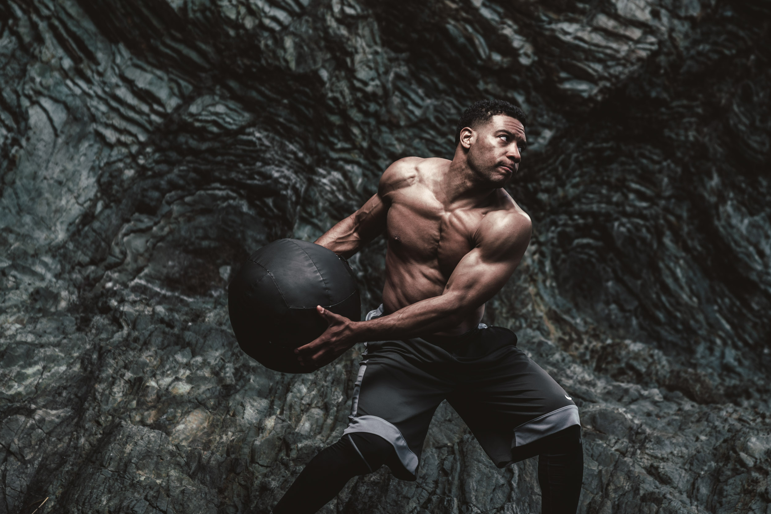 Male athlete with no shirt swings heavy medicine ball while working out on the rocky Tennessee Beach