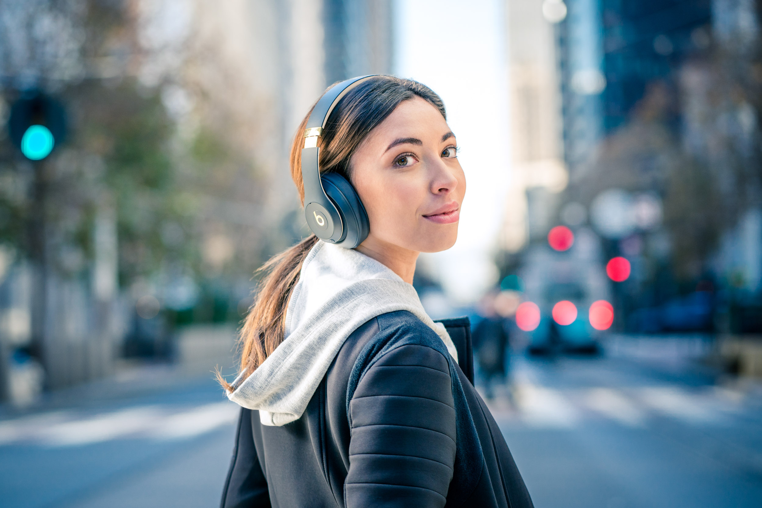 Female wearing Beats headphones looks over her shoulder while crossing street in San Francisco