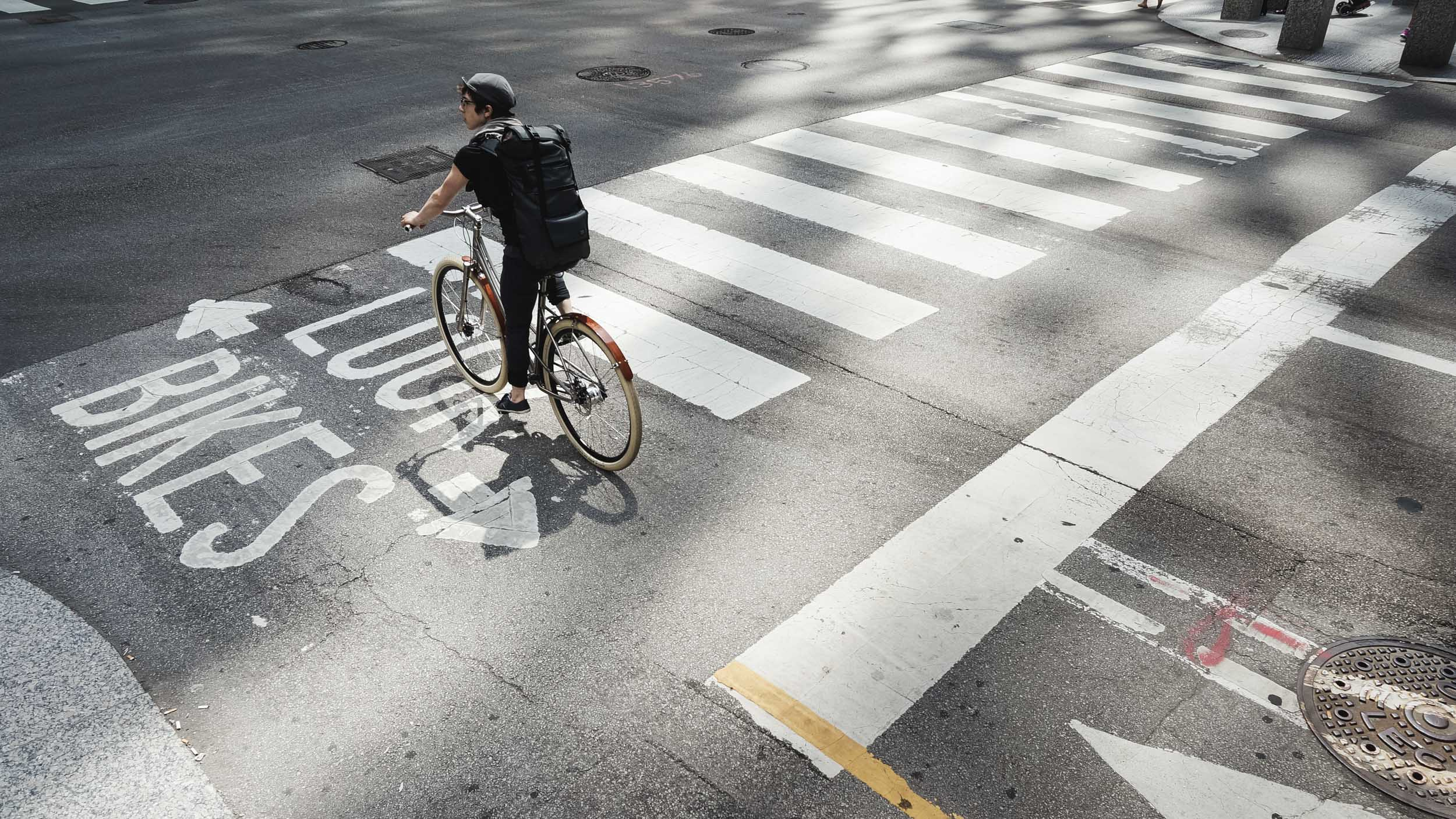 Female cyclist with backpack waits at crosswalk on her Budnitz bicycle in downtown Chicago