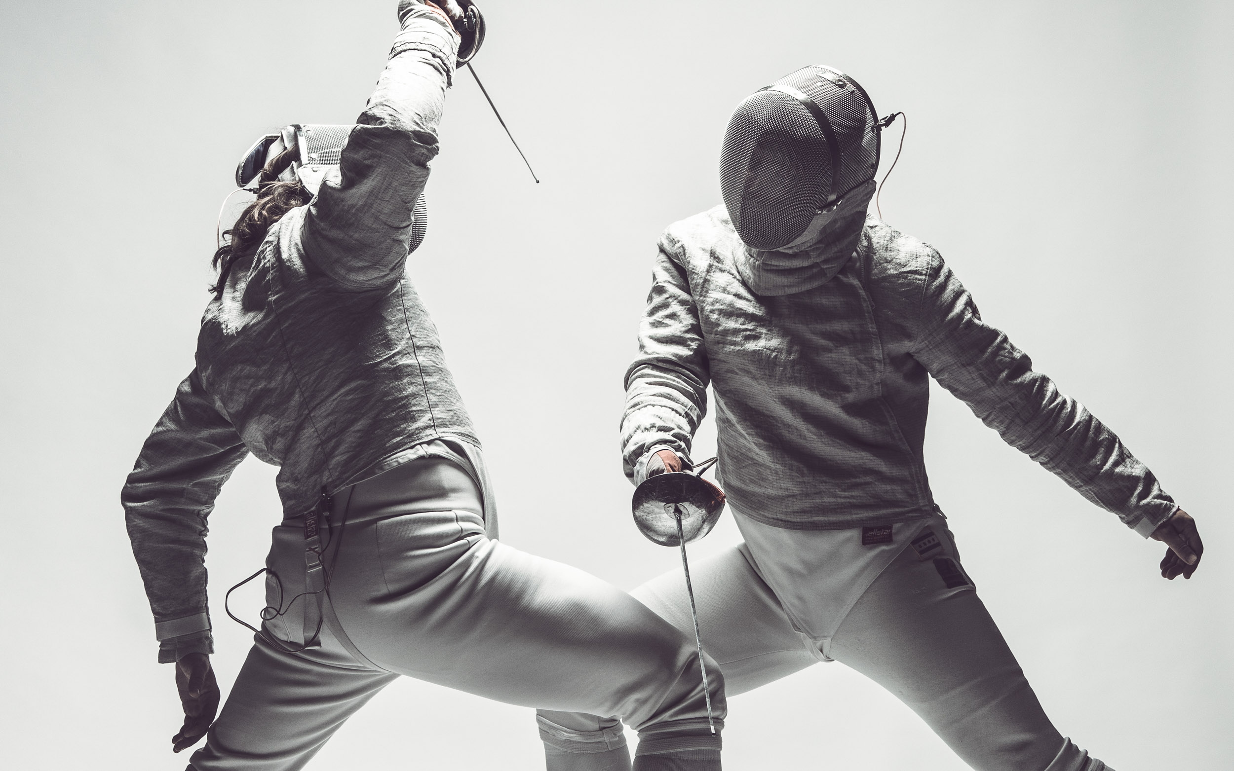 Two fencers in white strike a dramatic pose during a match