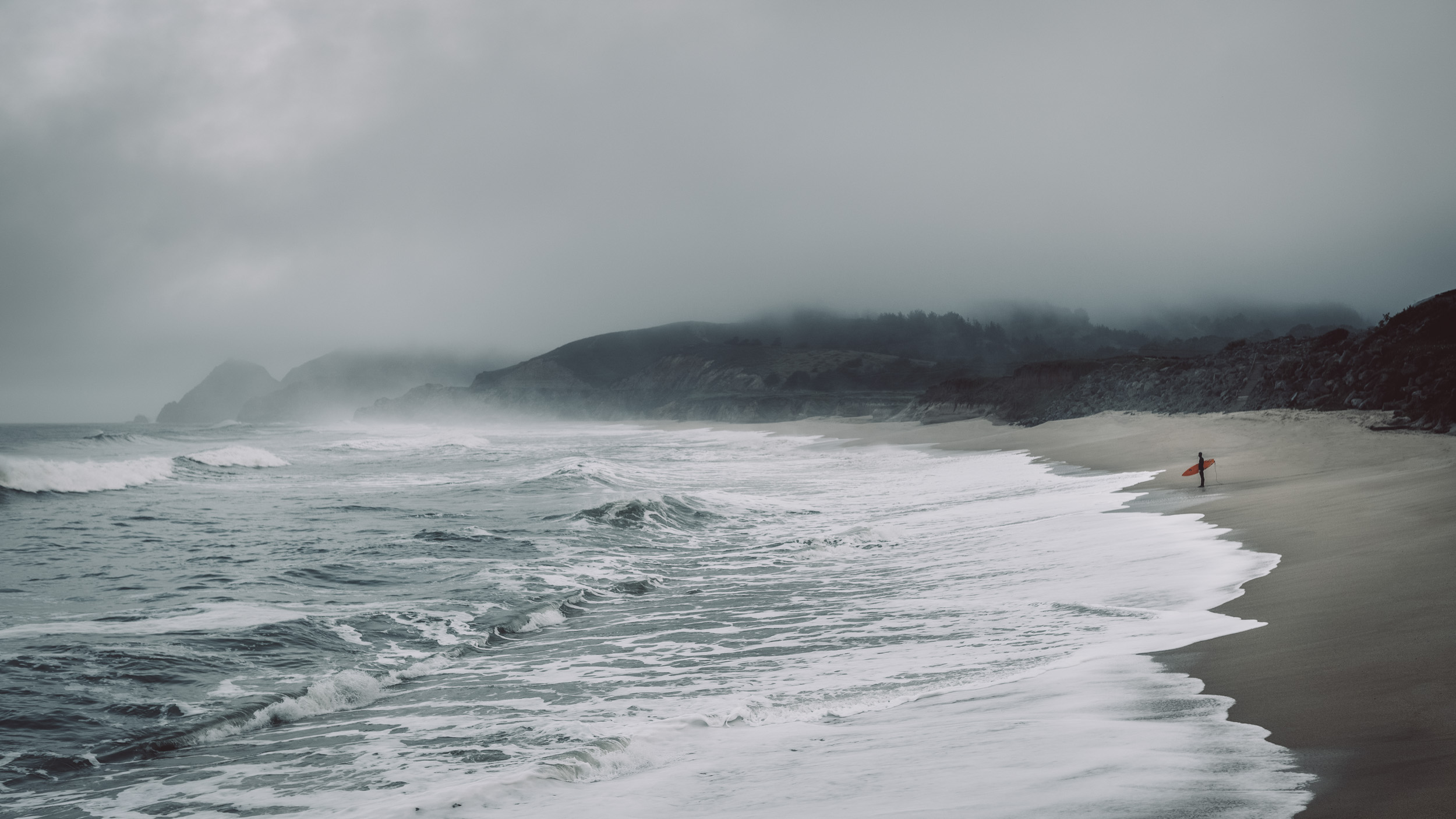 A lone male surfer with red surfboard stands on a wild and foggy beach with huge waves