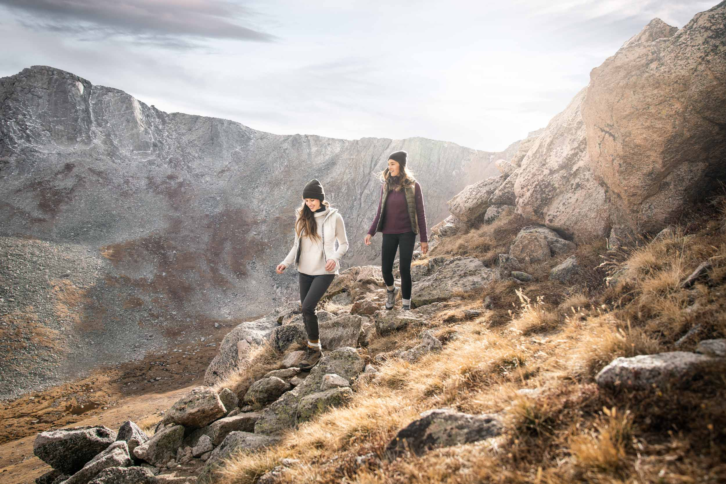 Two female hikers walk down a rocky path covered in golden grass near Mount Evans Colorado