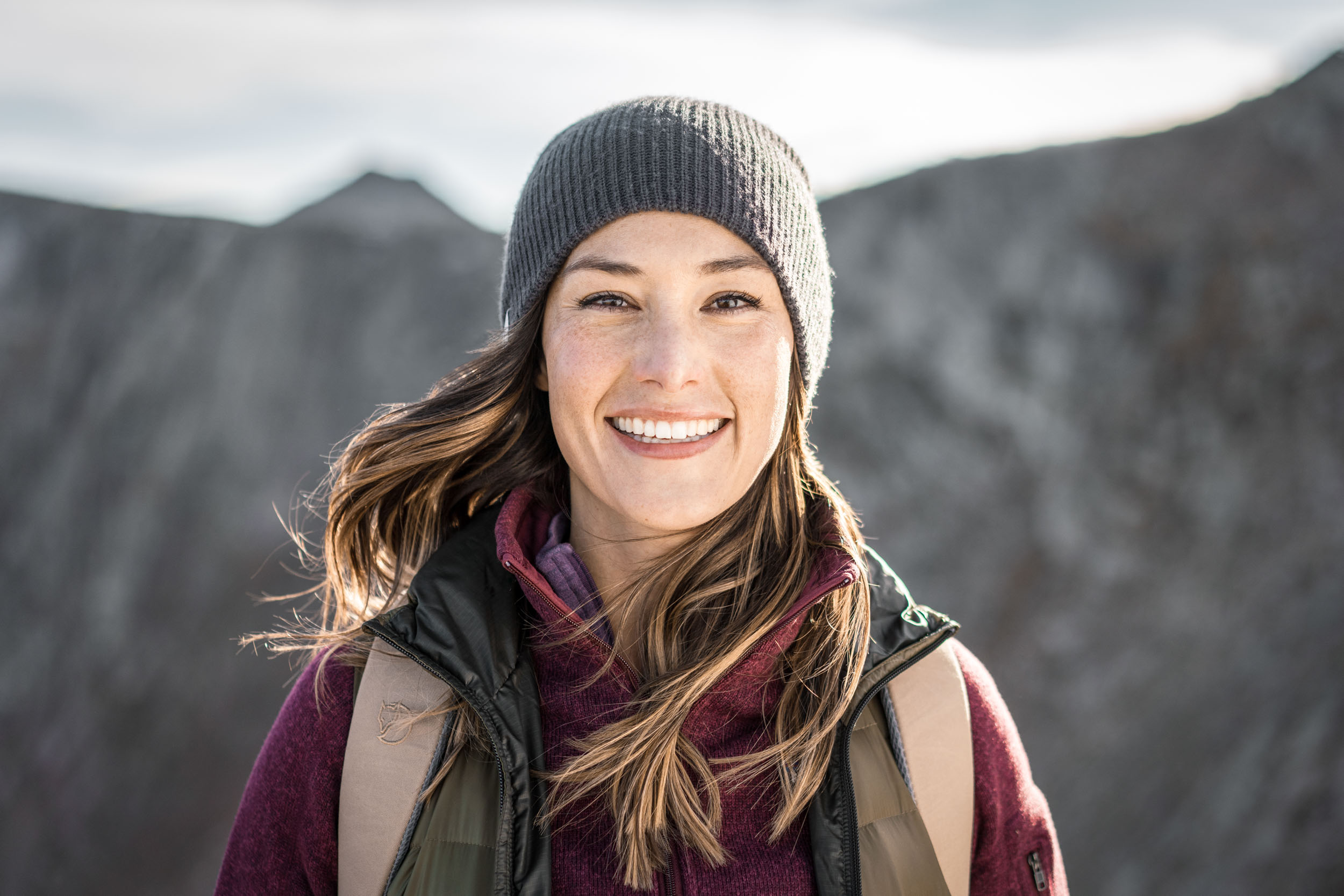 Portrait of female hiker wearing backpack and vest on a windy day on Mount Evans