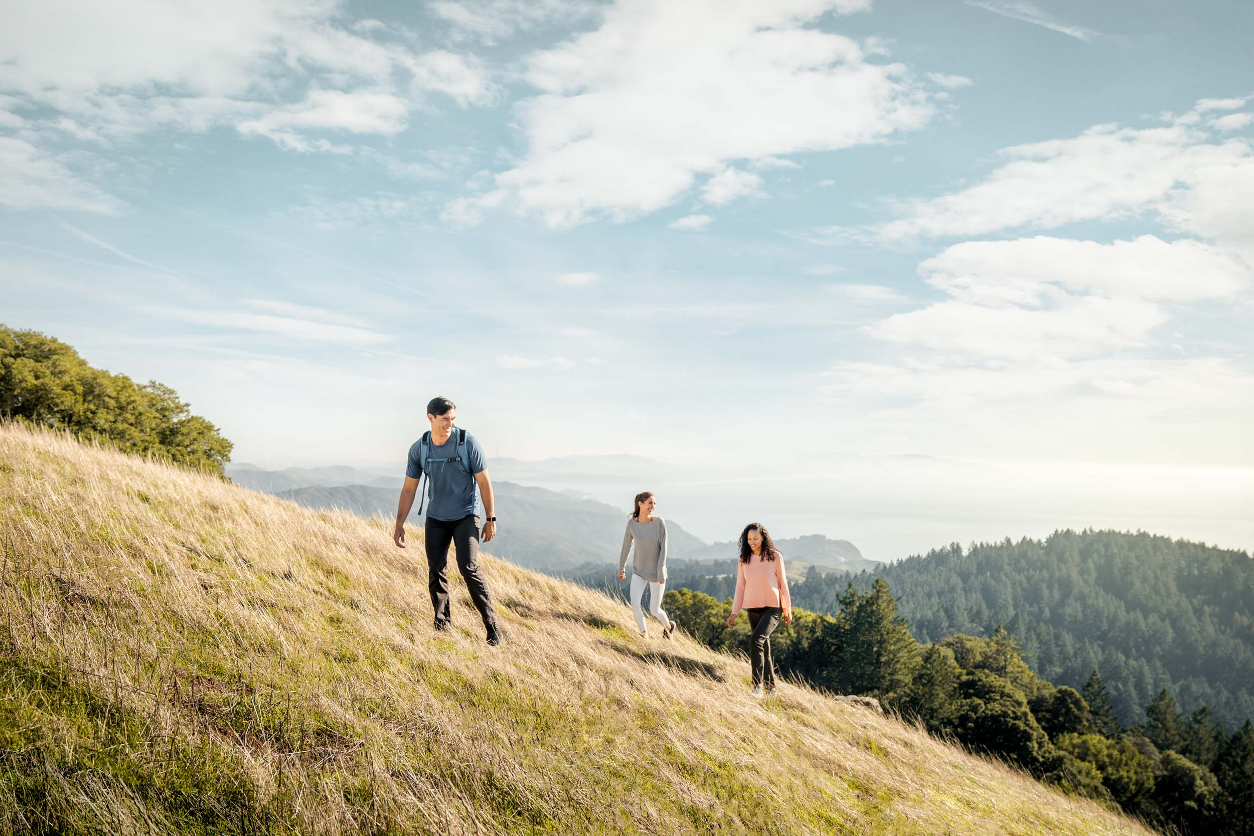 Three friends walk up a hill on tall golden grass near Mt Tam with the ocean in the background