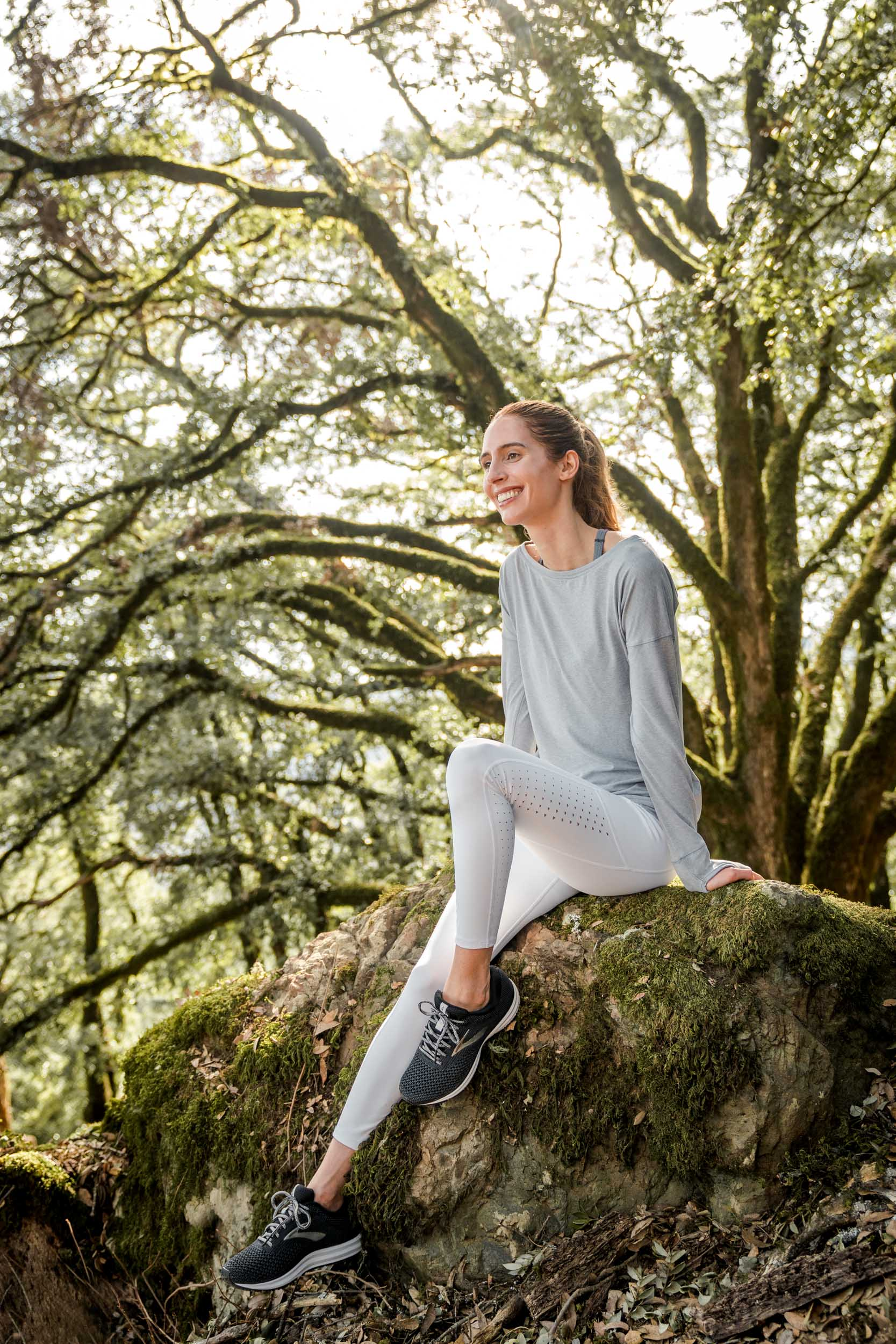 A female hiker sits on a mossy rock under a huge oak tree in California