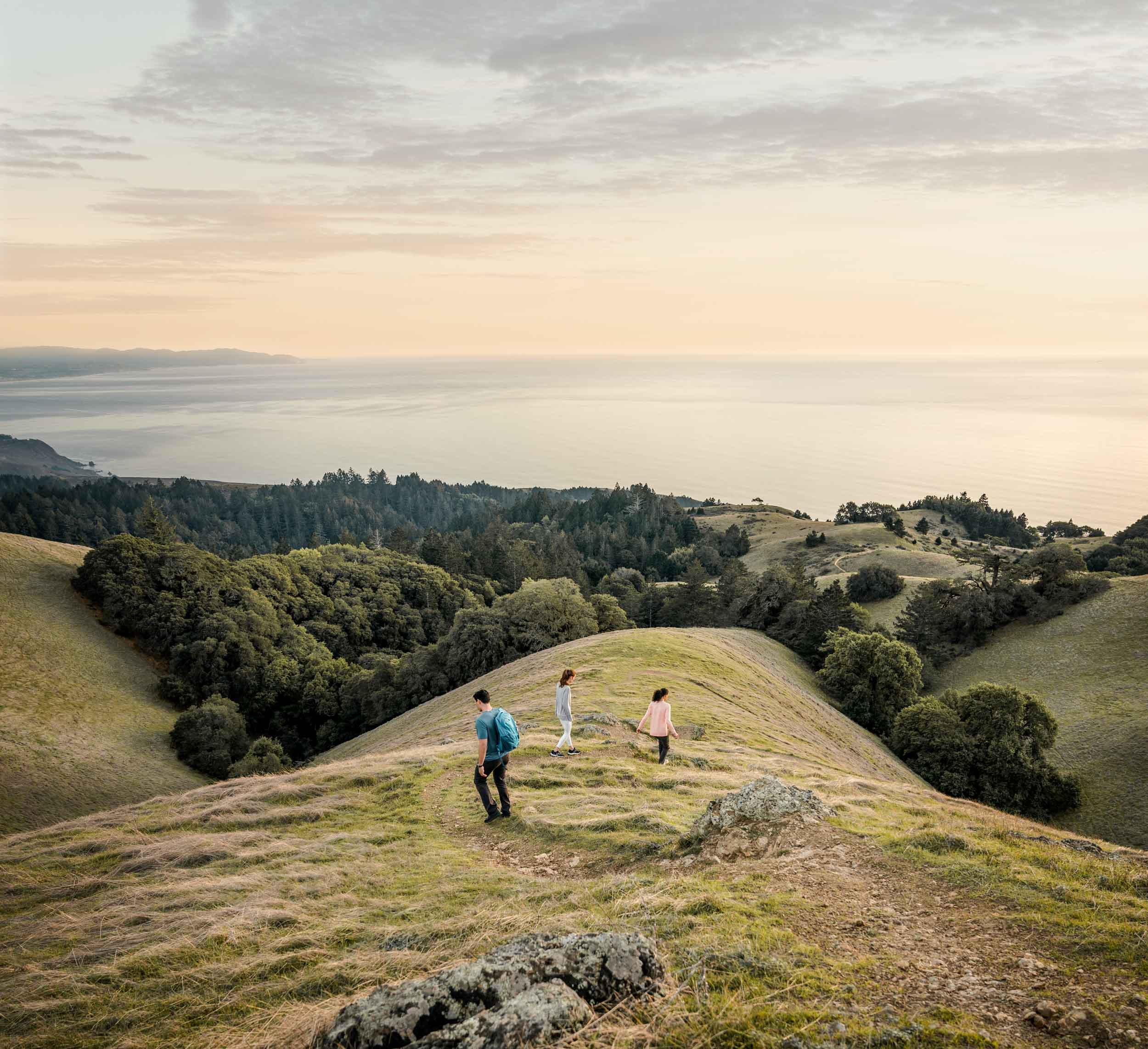 Three friends walk down a winding path high above the Pacific Ocean