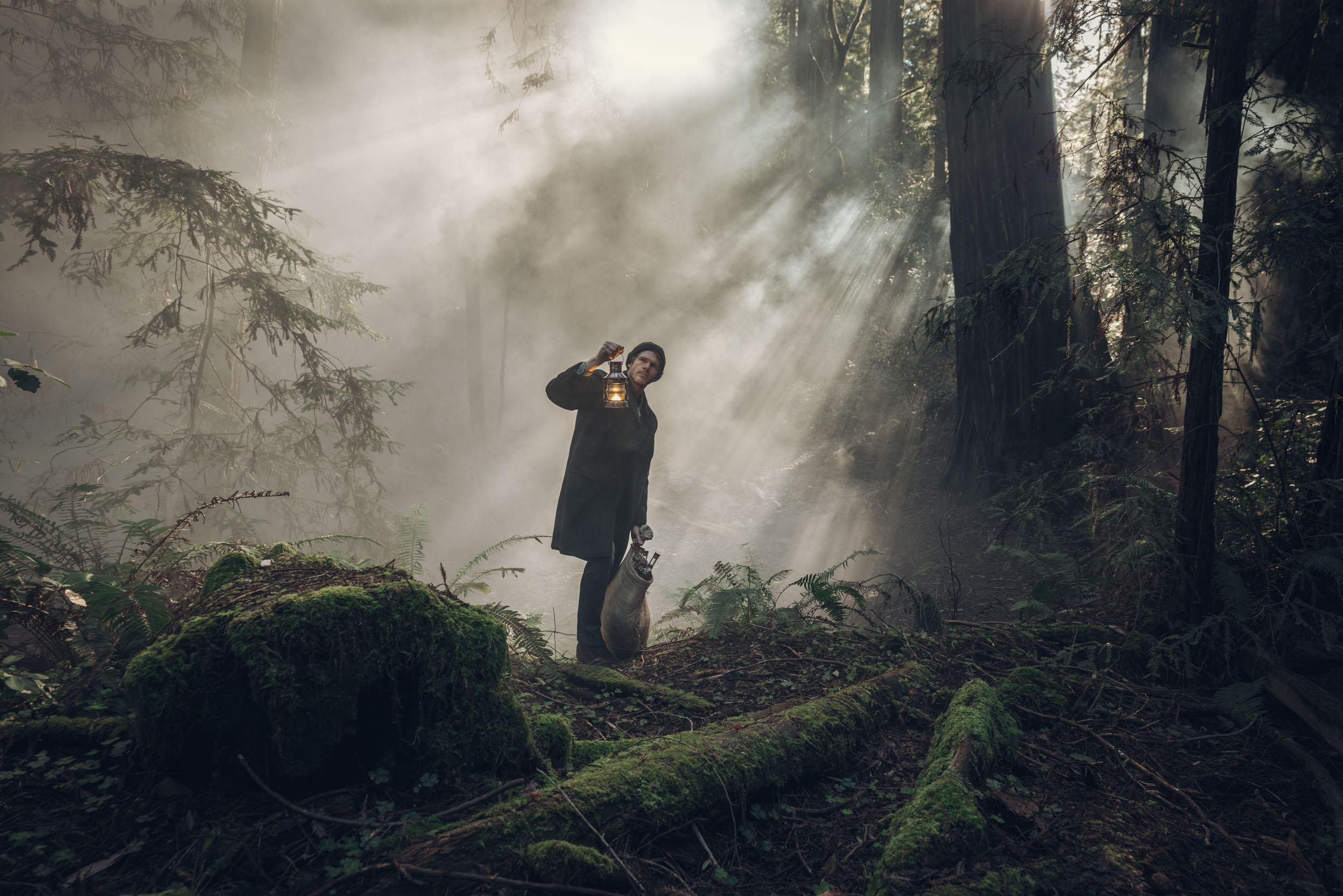 Man in dark clothes holds a lantern and peers through the fog in a creepy forest