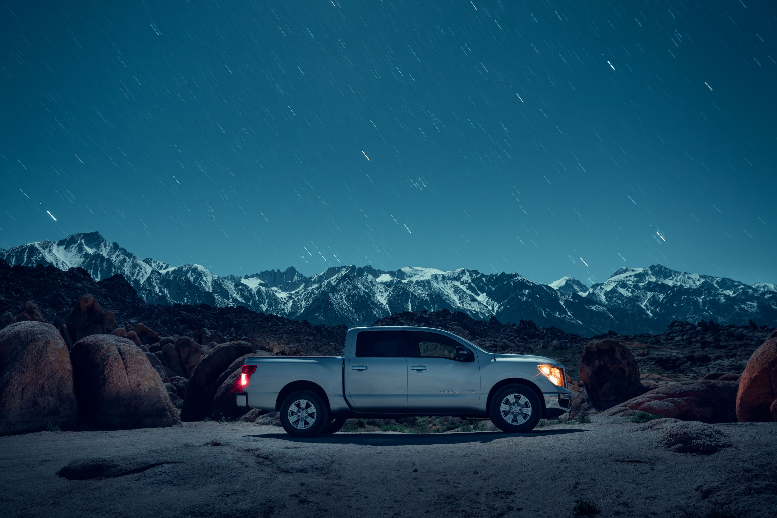 Silver Nissan pickup truck in the Alabama Hills desert at night in front of Mt Whitney full of stars.
