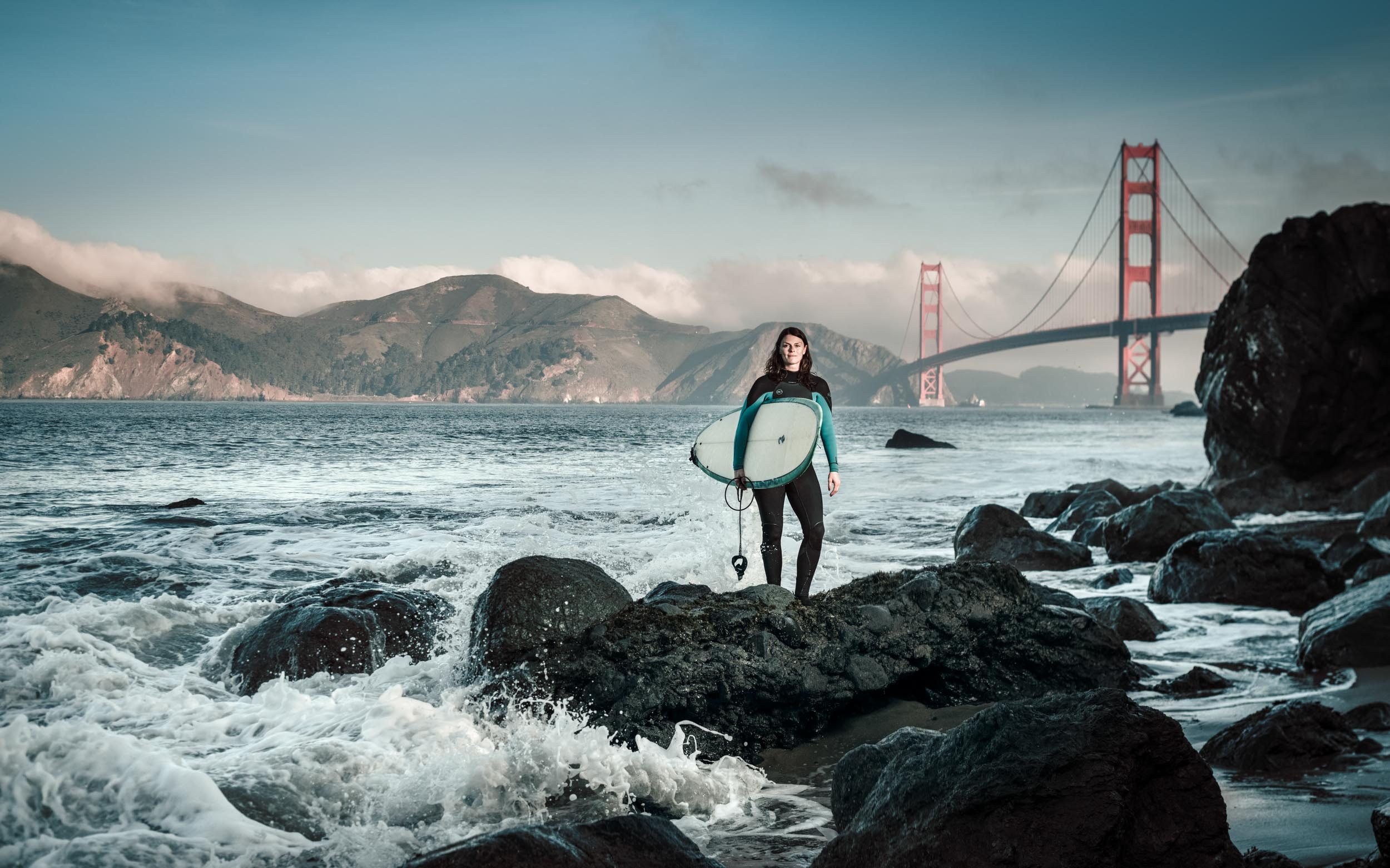 A female surfer walks out of ocean after surfing under the Golden Gate Bridge
